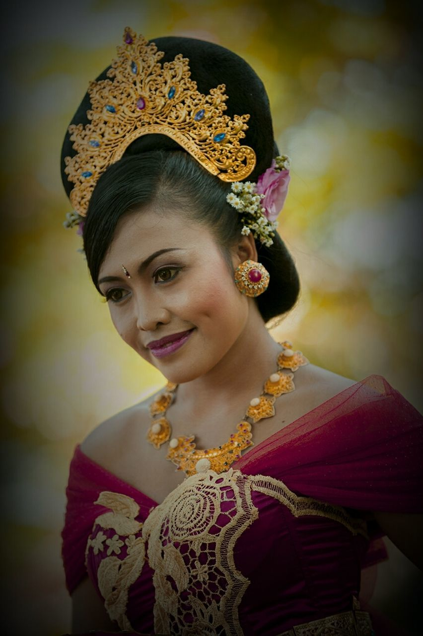 traditional clothing, one person, celebration, looking at camera, real people, lifestyles, young adult, portrait, front view, smiling, tradition, wearing flowers, beautiful woman, young women, leisure activity, happiness, standing, flower, outdoors, day, tiara, close-up, bride