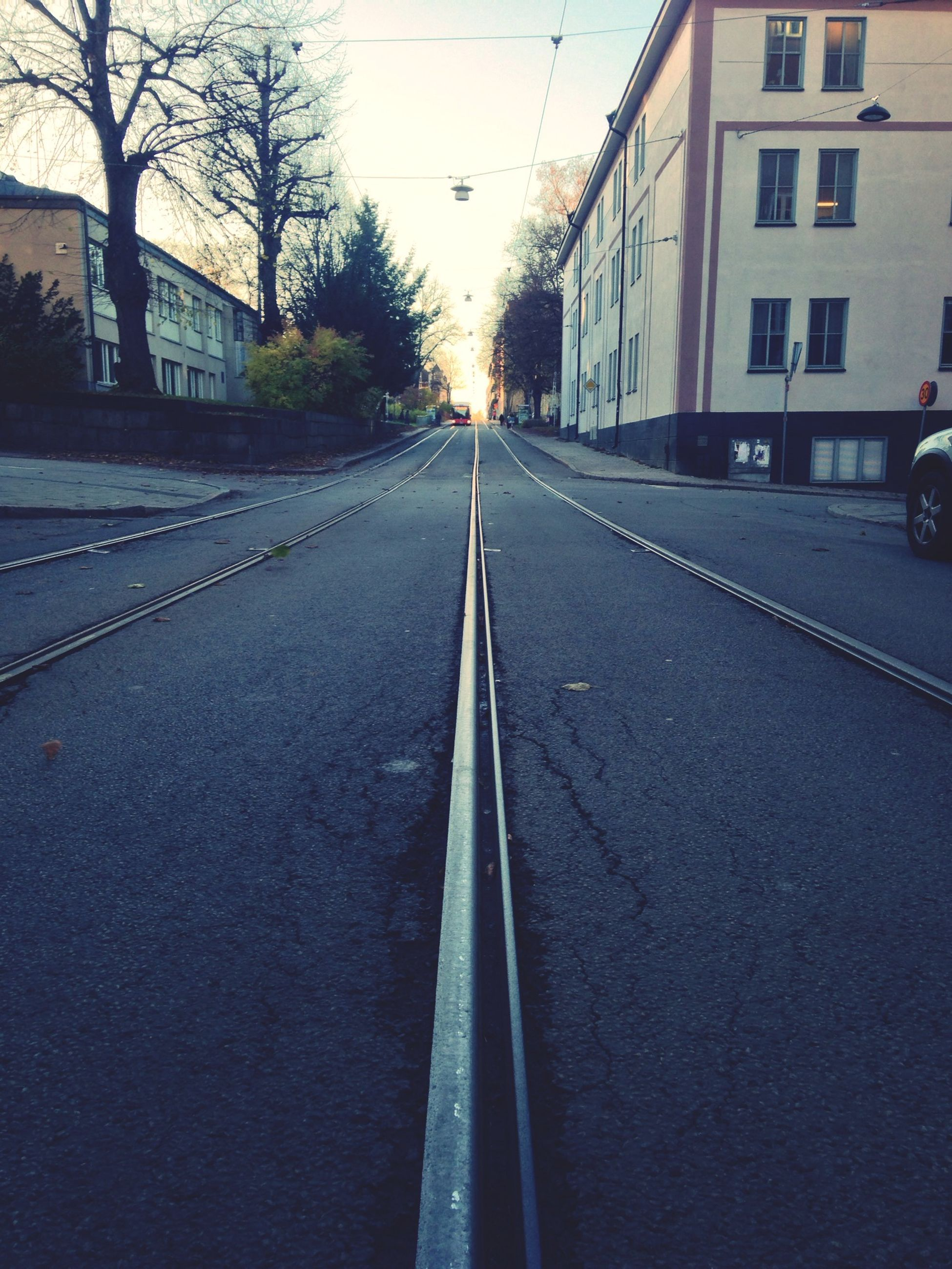 transportation, architecture, built structure, mode of transport, building exterior, the way forward, land vehicle, car, road, high angle view, city, street, diminishing perspective, road marking, railroad track, on the move, travel, vanishing point, day, sky