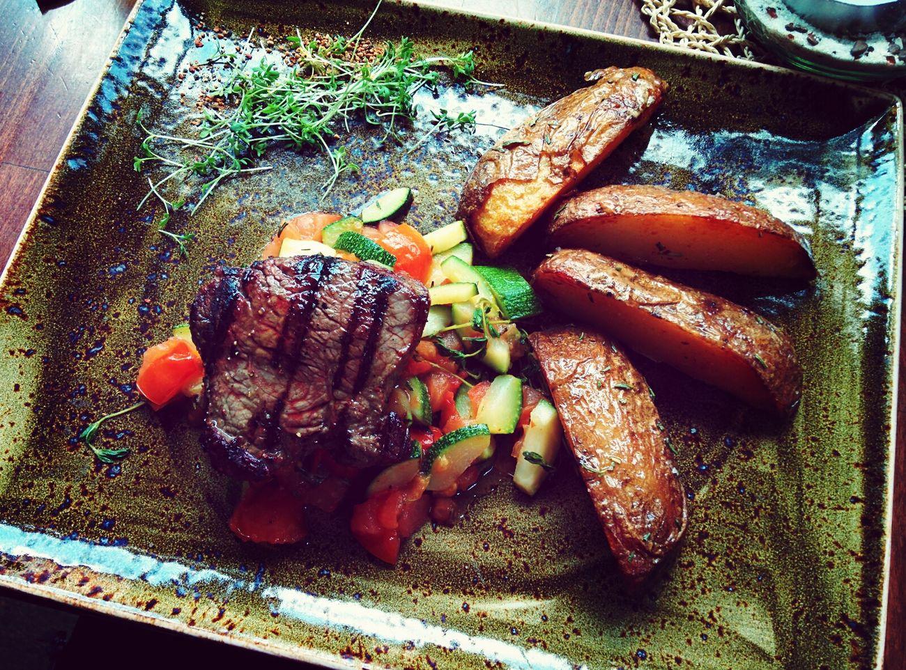 Kleines Spielzeug-Steak auf frischem Gemüse
