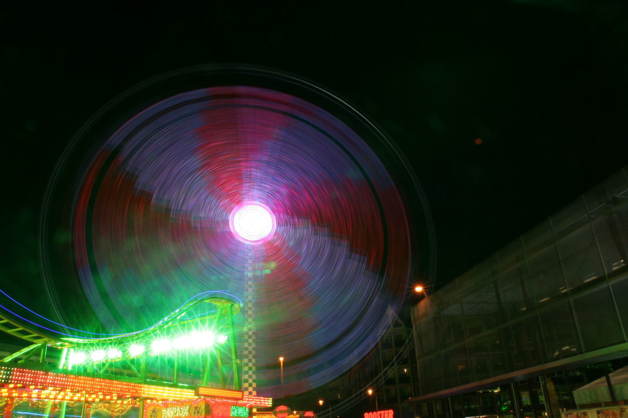 Low Angle View Of Illuminated Spinning Ferris Wheel At Night