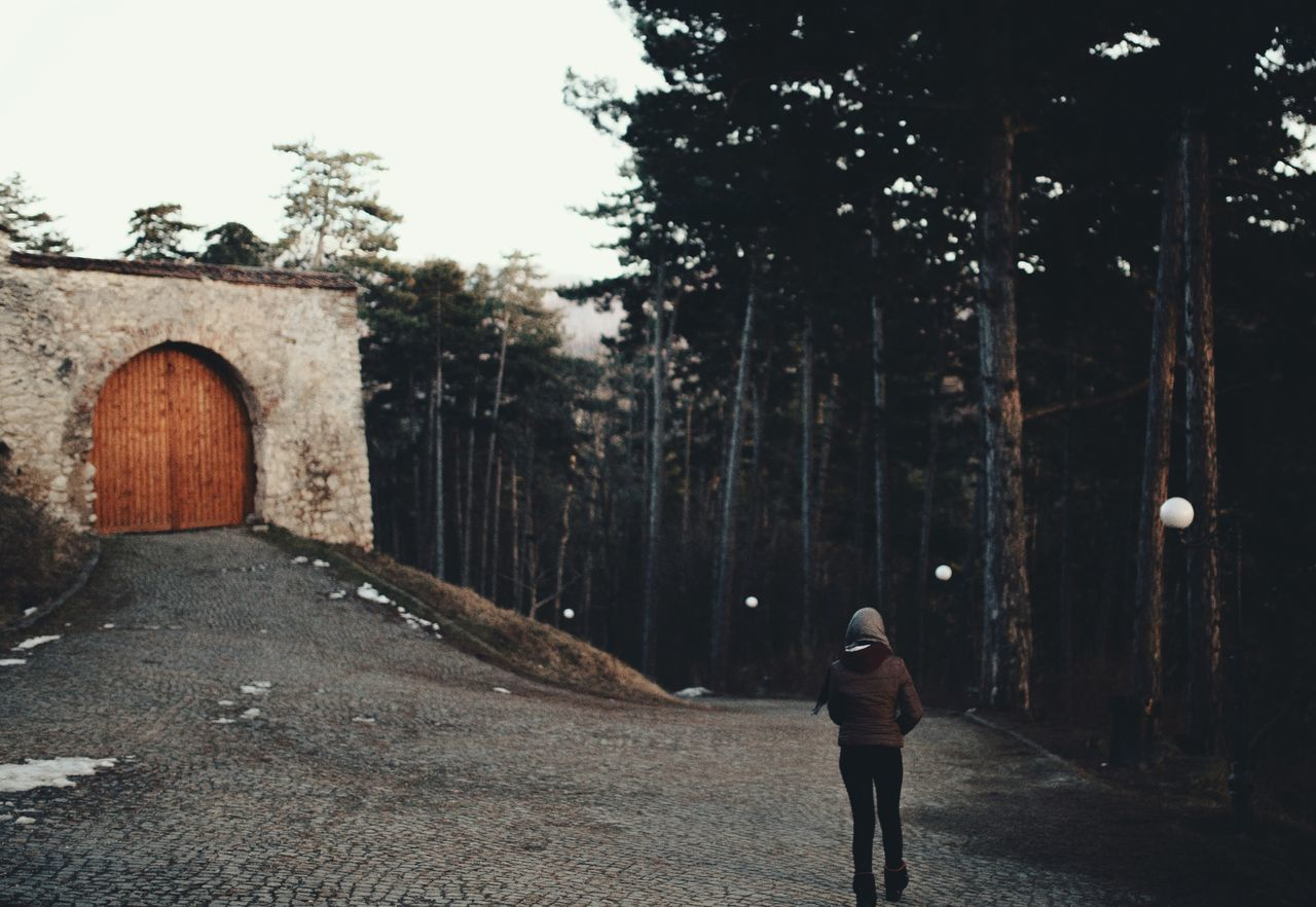 One Person Adults Only Lifestyles Outdoors Rear View People Warm Clothing Leisure Activity Tree Road Woman Walking Around Wall - Building Feature Nature Outdoor Photography Person People Photography People And Places VSCO Women Standing Natural Light
