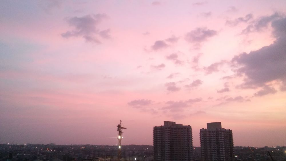 Robot-looking crane from afar. EyeEmNewHere Crane City Sunset Urban Skyline Sky No People Cranes And Construction Cotton Candy Sky