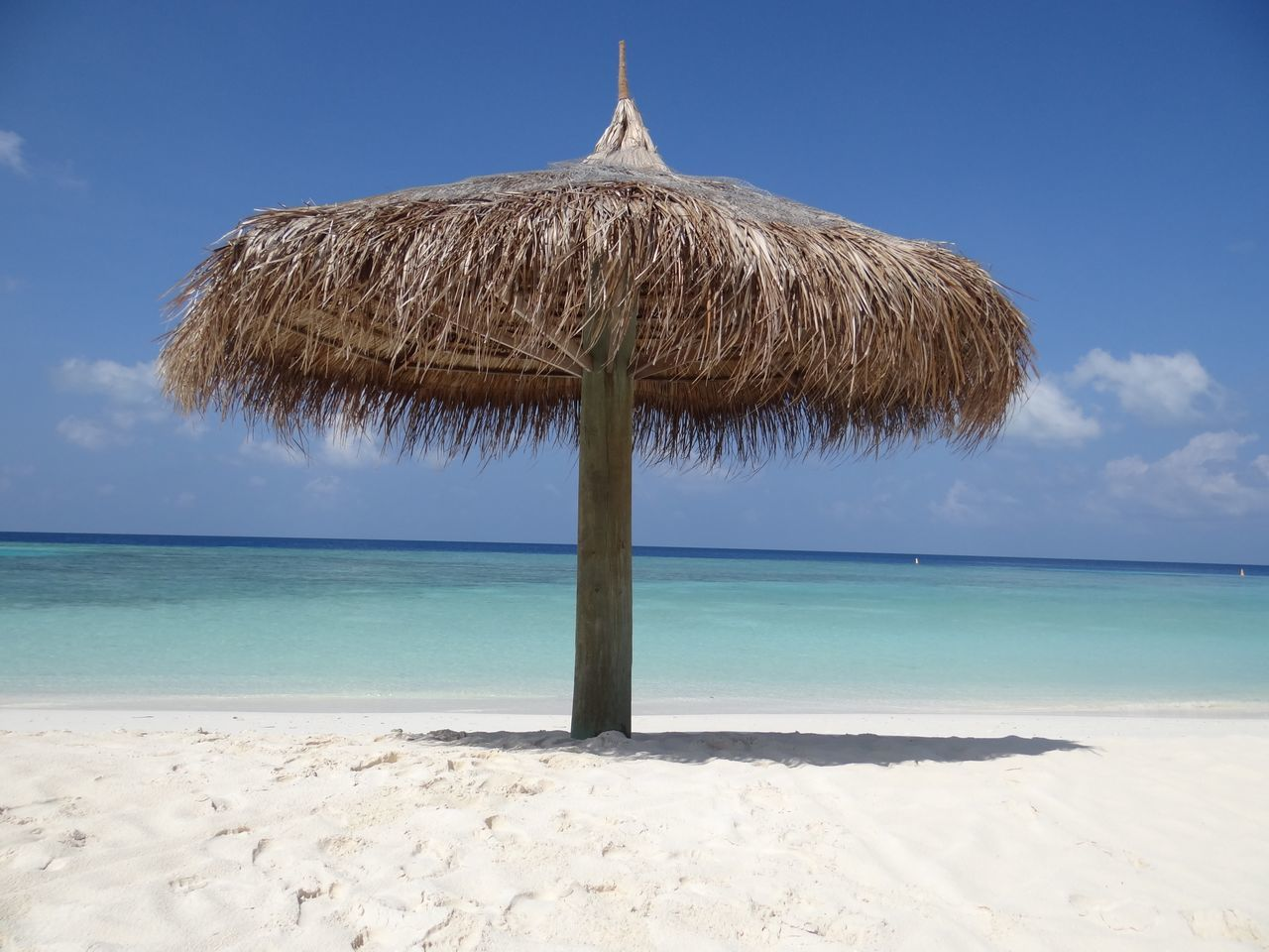 Thatched roof umbrella at beach against sky on sunny day