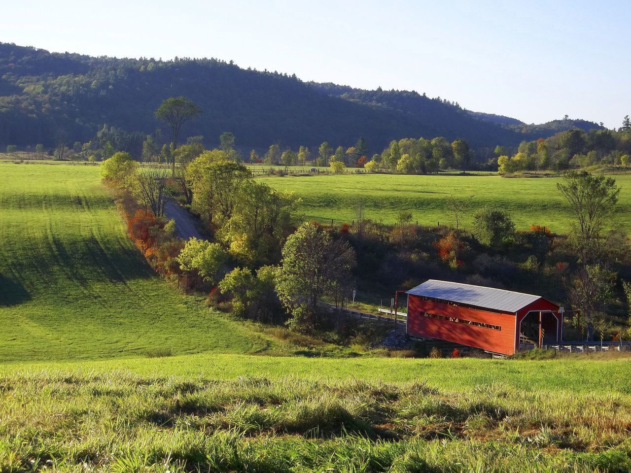 The covered bridge over the creek during the height of summer in the hills . Agriculture Beautiful Countryside Beauty In Nature Covered Bridge Covered Bridges Day Farm Field Grass Green Color Growth Hay Bale Idyllic Landscape Meadow Mountains Nature No People Outdoors Rural Scene Scenics Sky Tranquil Scene Tranquility Tree