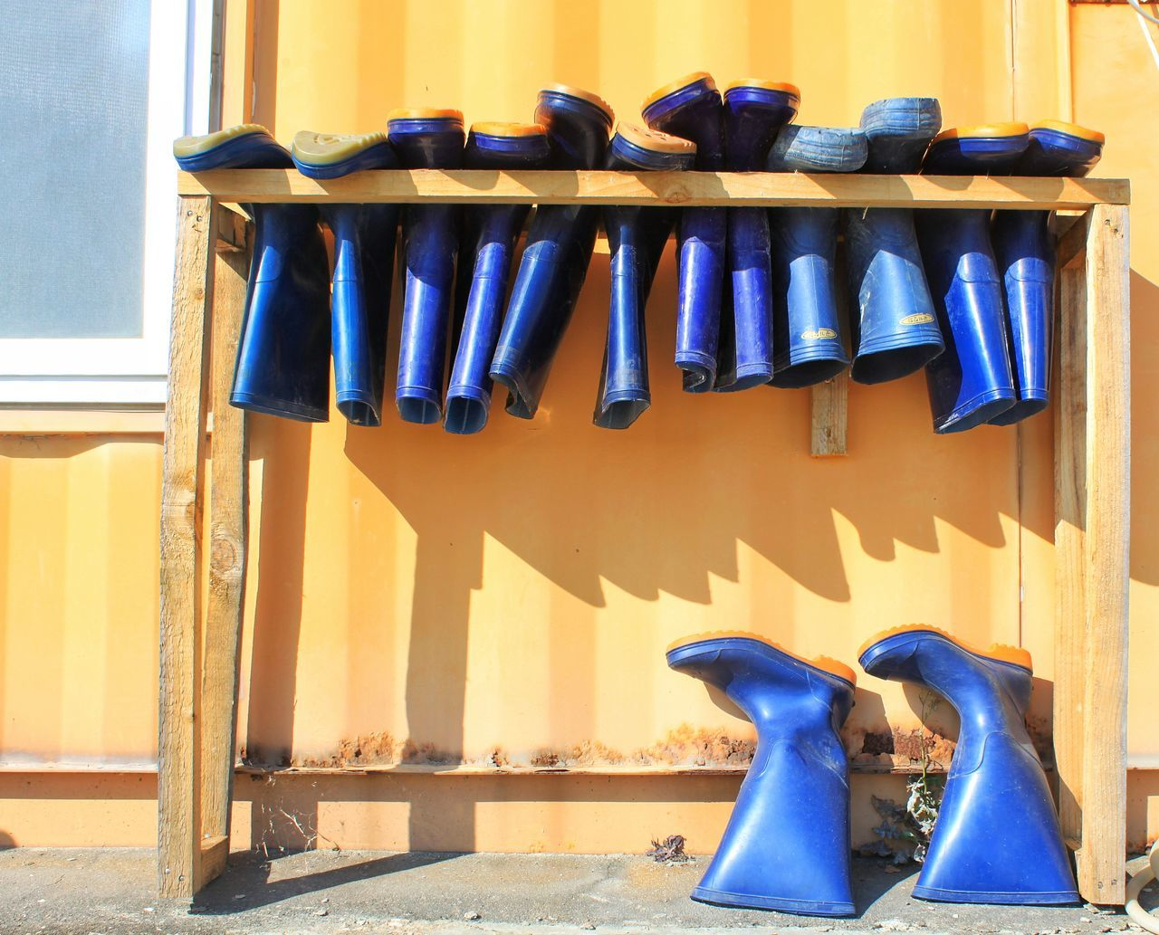 Blue Rubber Boots On Wooden Structure Against Wall