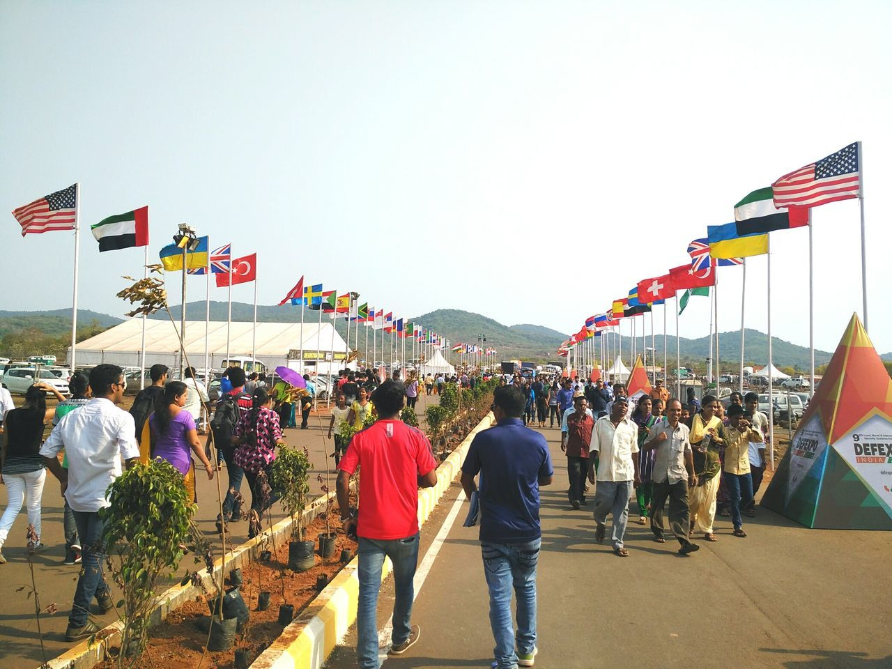The national flags of all the counties participating in the DefExpo 2016 raised at the site of defence exhibition in Quitol. National Flags Countries Participating Defexpo Defexpo 2016 Defexpogoa2016 Quitol Goa India Goa India Waving Flags Wind Windy Day People Walking Entryway Indian Army Military Defence Expo Public Crowd Defence Event Defence Expo Defence Exposition