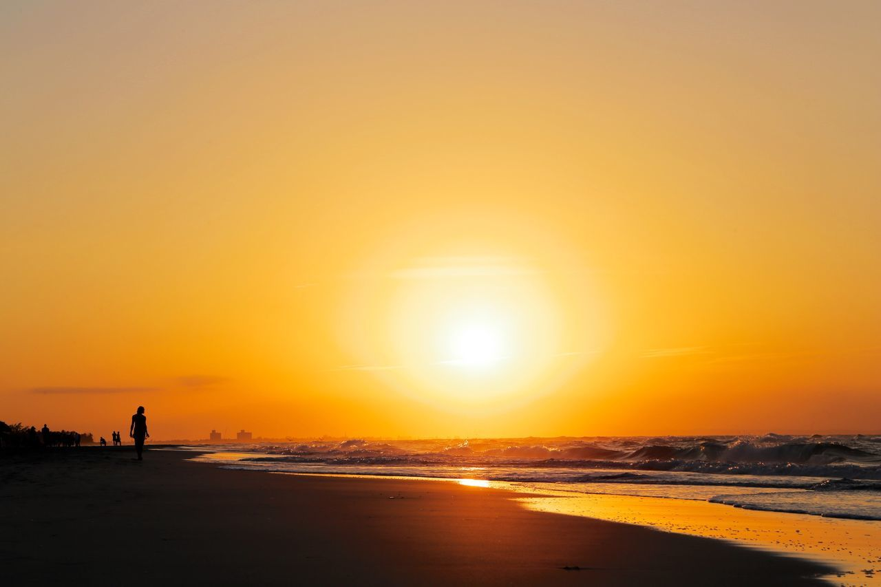 sunset, sea, beach, orange color, beauty in nature, sun, nature, silhouette, scenics, one person, shore, sand, real people, tranquil scene, tranquility, leisure activity, outdoors, water, sky, standing, full length, walking, horizon over water, sunlight, lifestyles, vacations, men, travel destinations, wave, clear sky, adult, people