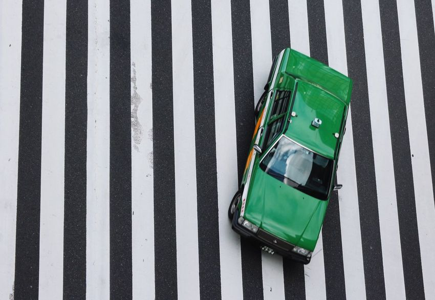 A Japanese green taxi car crossing the crosswalk Striped Zebra Crossing Transportation Road Marking Street Suitcase High Angle View Road Green Color Luggage Mode Of Transport Car Dividing Line Outdoors Asphalt Land Vehicle City Pedestrian Day Zebra Taxi Japan