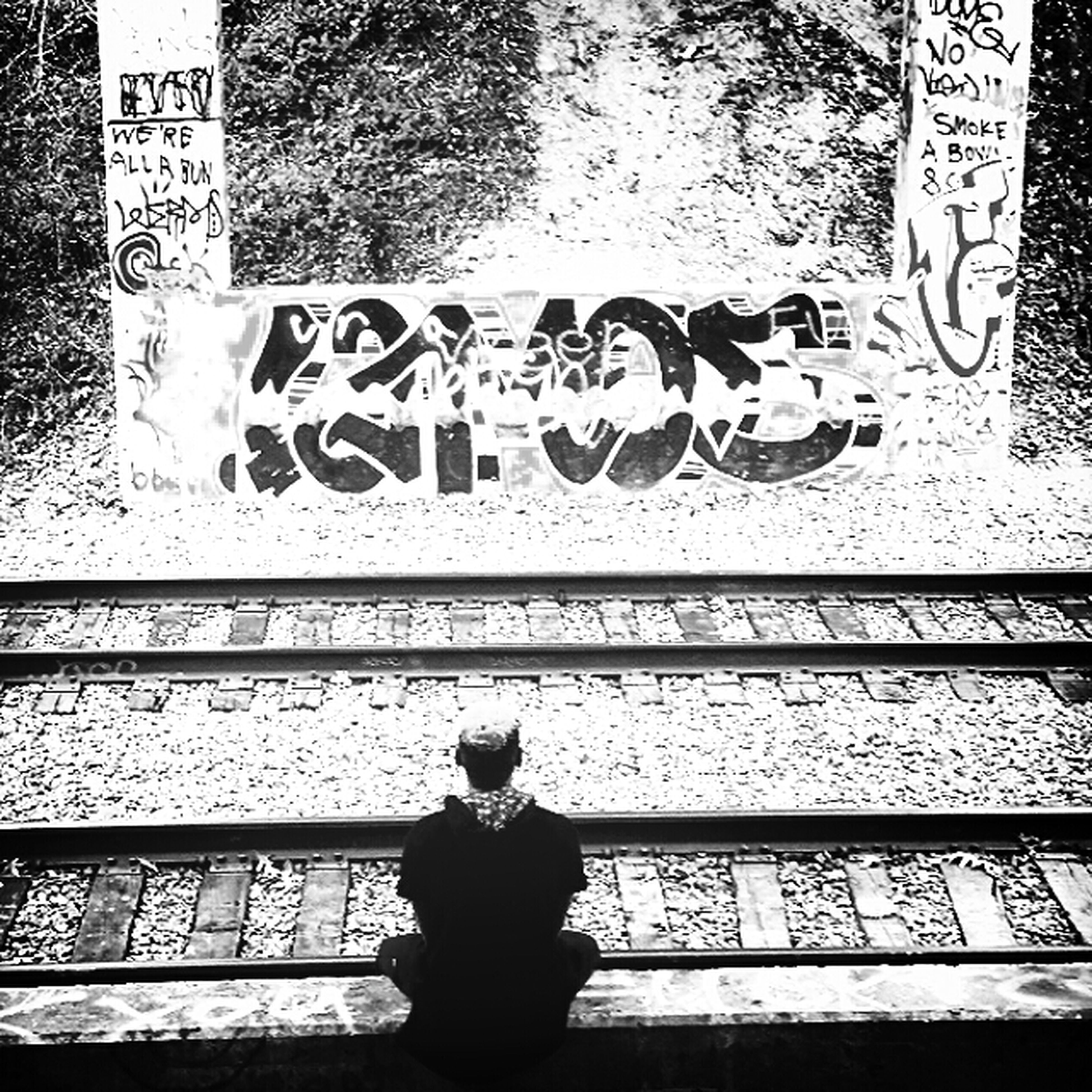 text, western script, communication, lifestyles, standing, wall - building feature, graffiti, leisure activity, three quarter length, built structure, non-western script, art, human representation, outdoors, day, architecture, building exterior, men