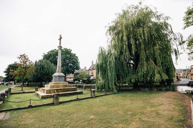 Stone cross and willow in a park near the river in Bourton on the Water a cloudy day of summer Beauty In Nature Blue Bourton On The Water Cloudy Cotswolds Cross Day Grass Green Color Growth Nature No People Outdoors Park Scenics Sky Stone Cross Tranquil Scene Tranquility Travel Destinations Tree Tree Trunk Willow