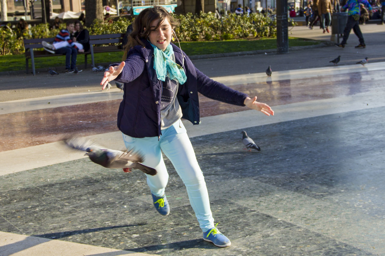 Teenage Girl With Arms Outstretched While Chasing Pigeon On Footpath