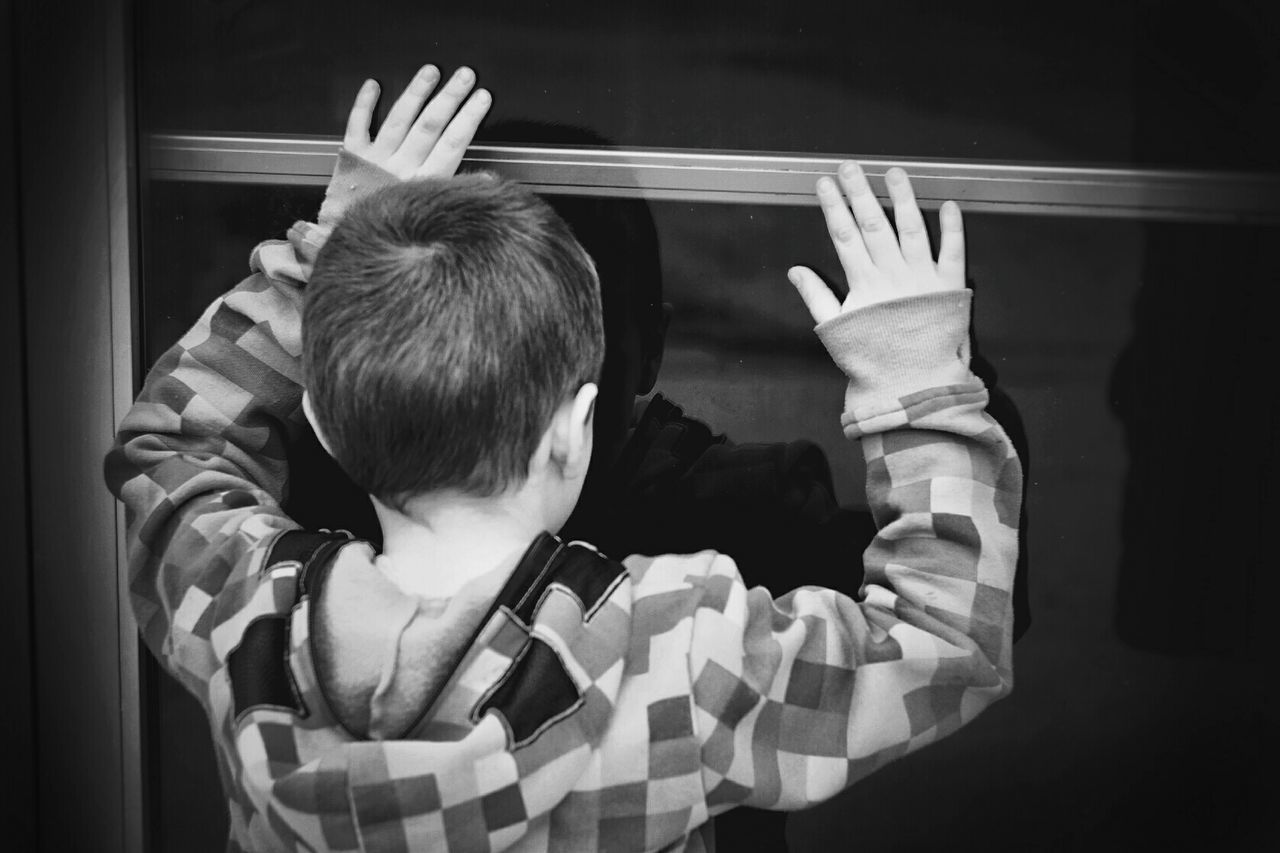 Rear View Of Boy Looking Through Glass Door