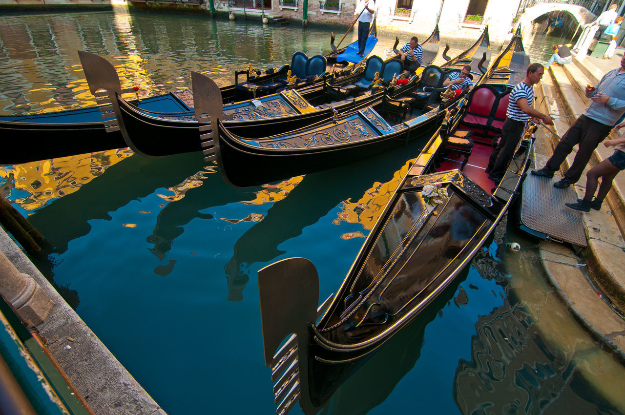 nautical vessel, water, transportation, gondola - traditional boat, canal, moored, mode of transport, reflection, gondola, boat, high angle view, waterfront, outdoors, day, rowboat, wooden post, gondolier, travel destinations, rowing, oar, no people, nature
