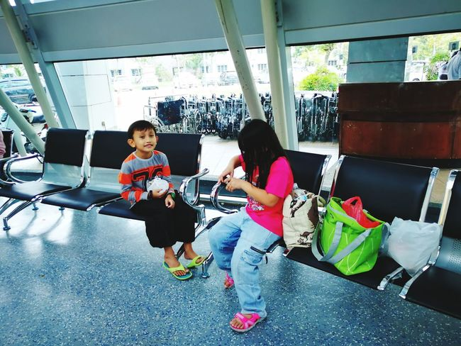 Young kids waiting at the bench of the hospital. Childhood Child Two People Full Length Togetherness Boys Casual Clothing Bonding People Day Playing Adult Indoors  Sitting Lifestyles Smiling Technology Wireless Technology Siblings Children Only Children Kids Cute Unschooling Happiness