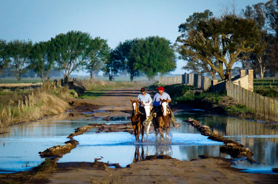 two horses with riders crossing a puddle of water on a dirt road The Photojournalist - 2015 EyeEm Awards