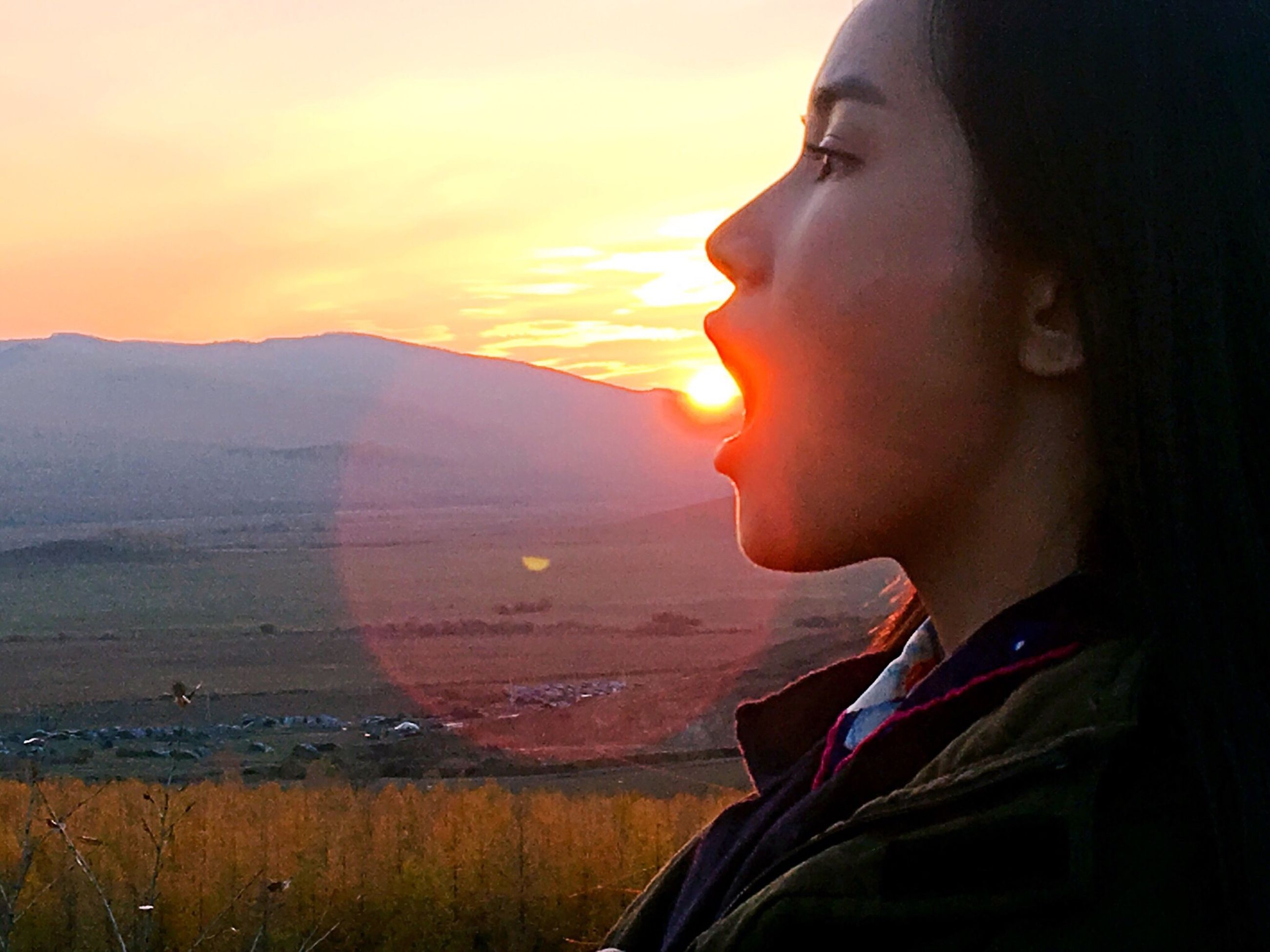 sunset, lifestyles, headshot, sky, leisure activity, young adult, orange color, sunlight, close-up, scenics, water, mountain, sun, contemplation, tranquil scene, person, tranquility, sunbeam, sea, beauty in nature, cloud - sky, outdoors, nature, journey