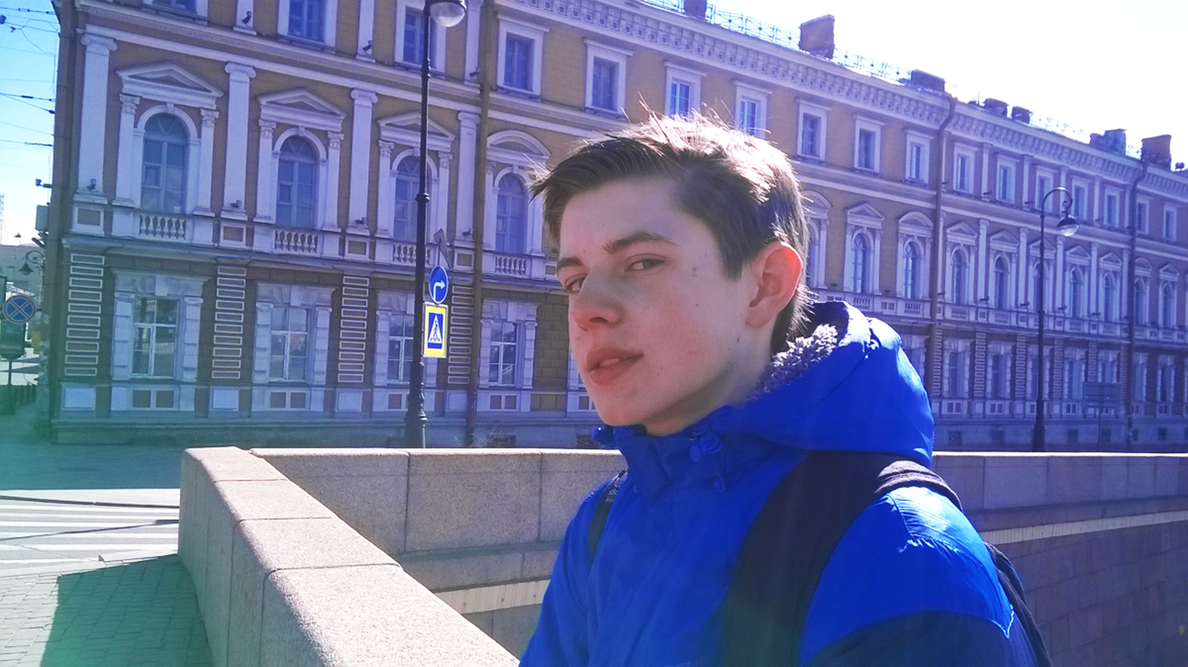 real people, architecture, built structure, one person, building exterior, lifestyles, leisure activity, young adult, young men, outdoors, day, casual clothing, headshot, side view, looking at camera, portrait, city, warm clothing, close-up