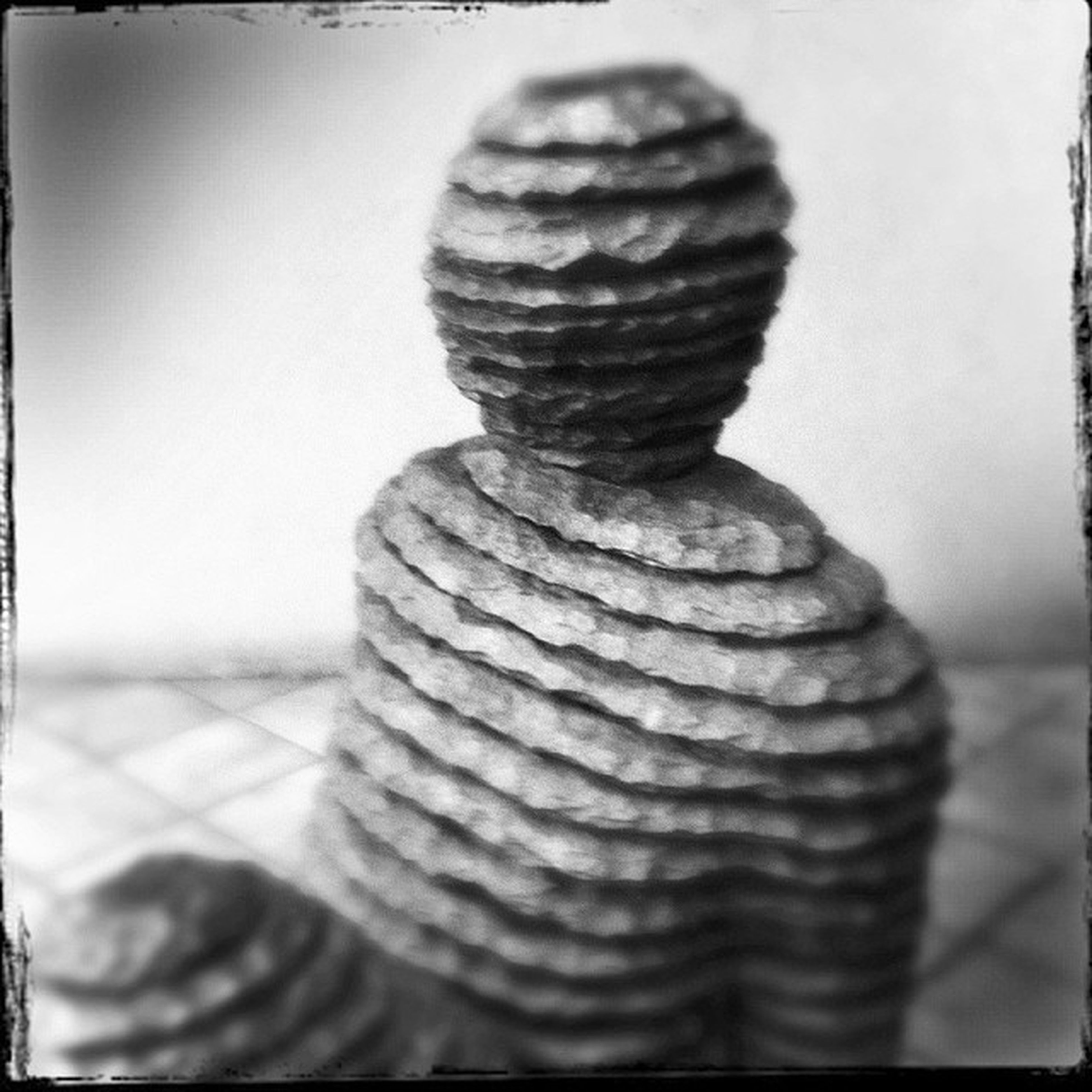 close-up, focus on foreground, indoors, transfer print, art and craft, still life, creativity, auto post production filter, balance, human representation, selective focus, art, rope, stack, one person, day, pattern, sculpture