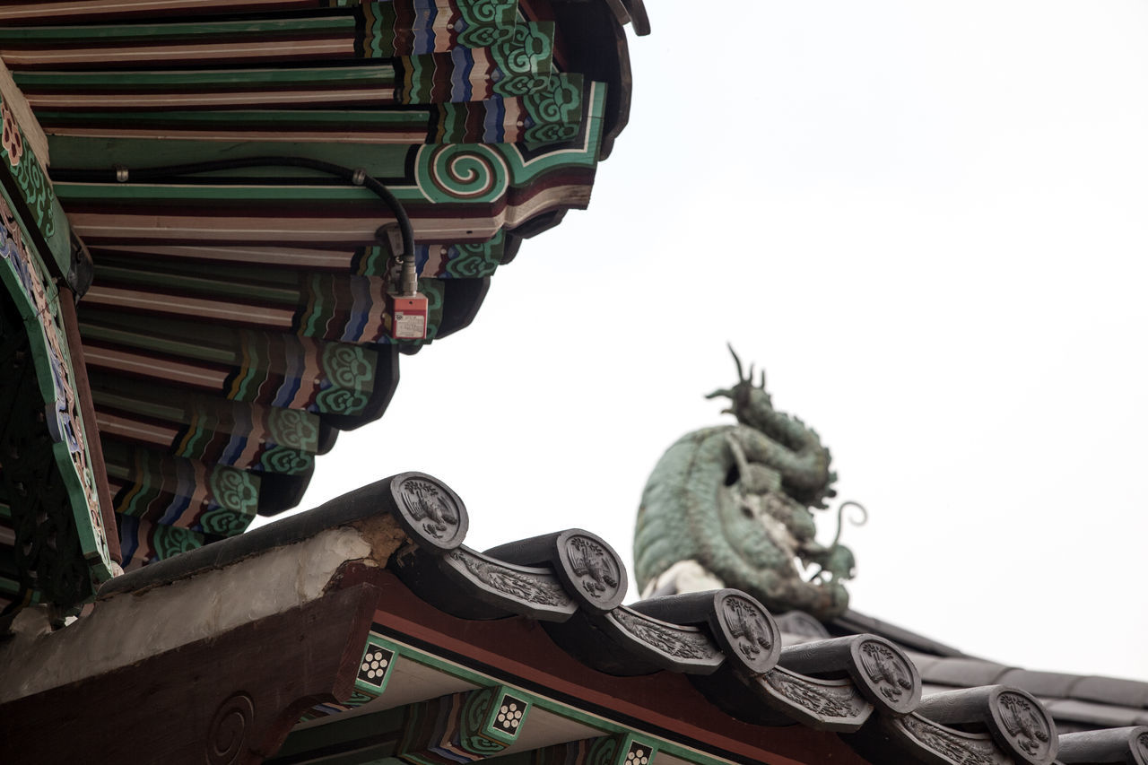 low angle view, building exterior, built structure, architecture, roof, clear sky, statue, place of worship, religion, day, spirituality, sculpture, eaves, outdoors, traditional building, dragon, history, no people, ancient, travel destinations, sky, chinese dragon