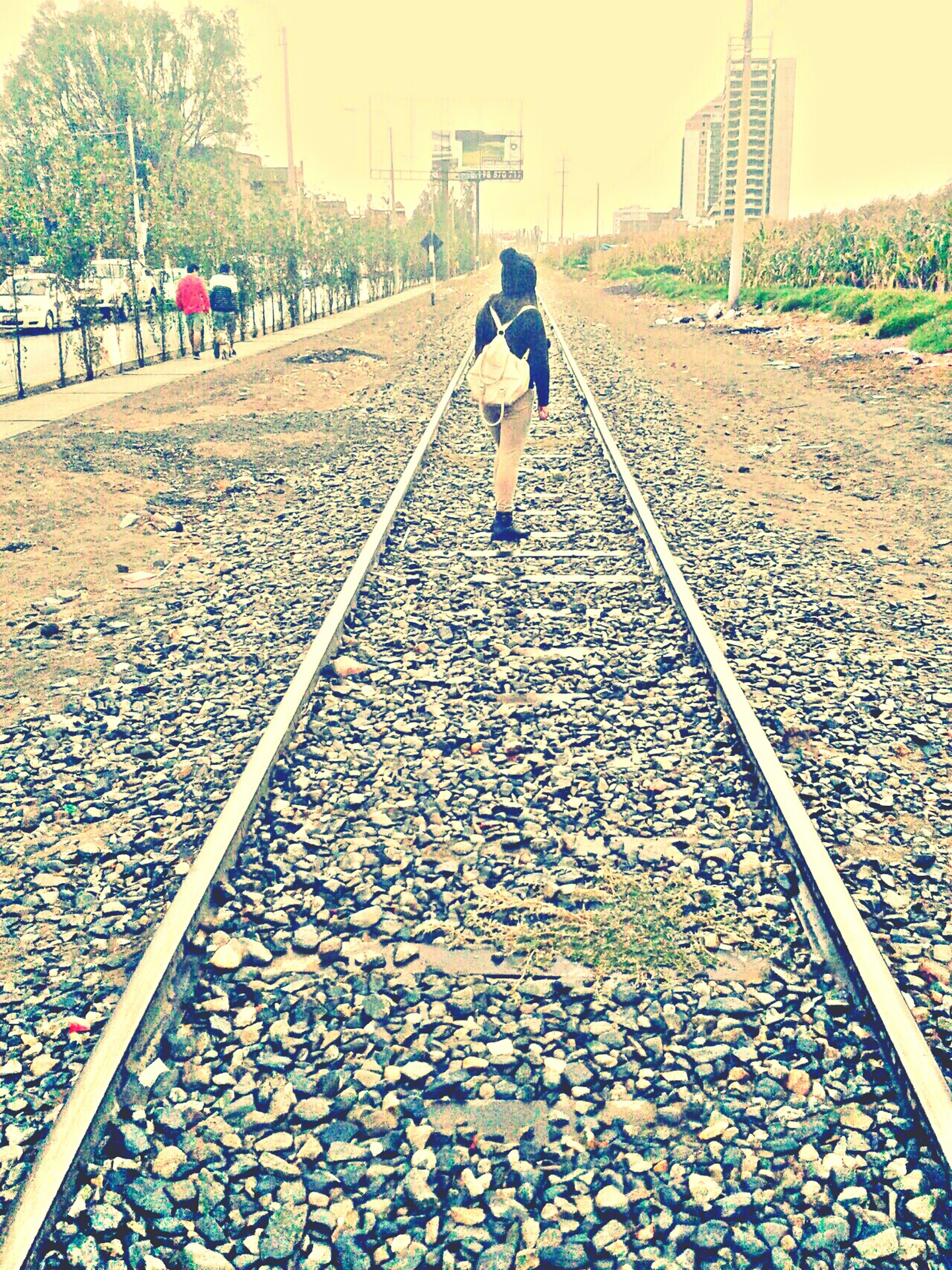 railroad track, the way forward, full length, walking, transportation, rear view, lifestyles, diminishing perspective, rail transportation, men, vanishing point, leisure activity, day, person, outdoors, gravel, casual clothing, surface level