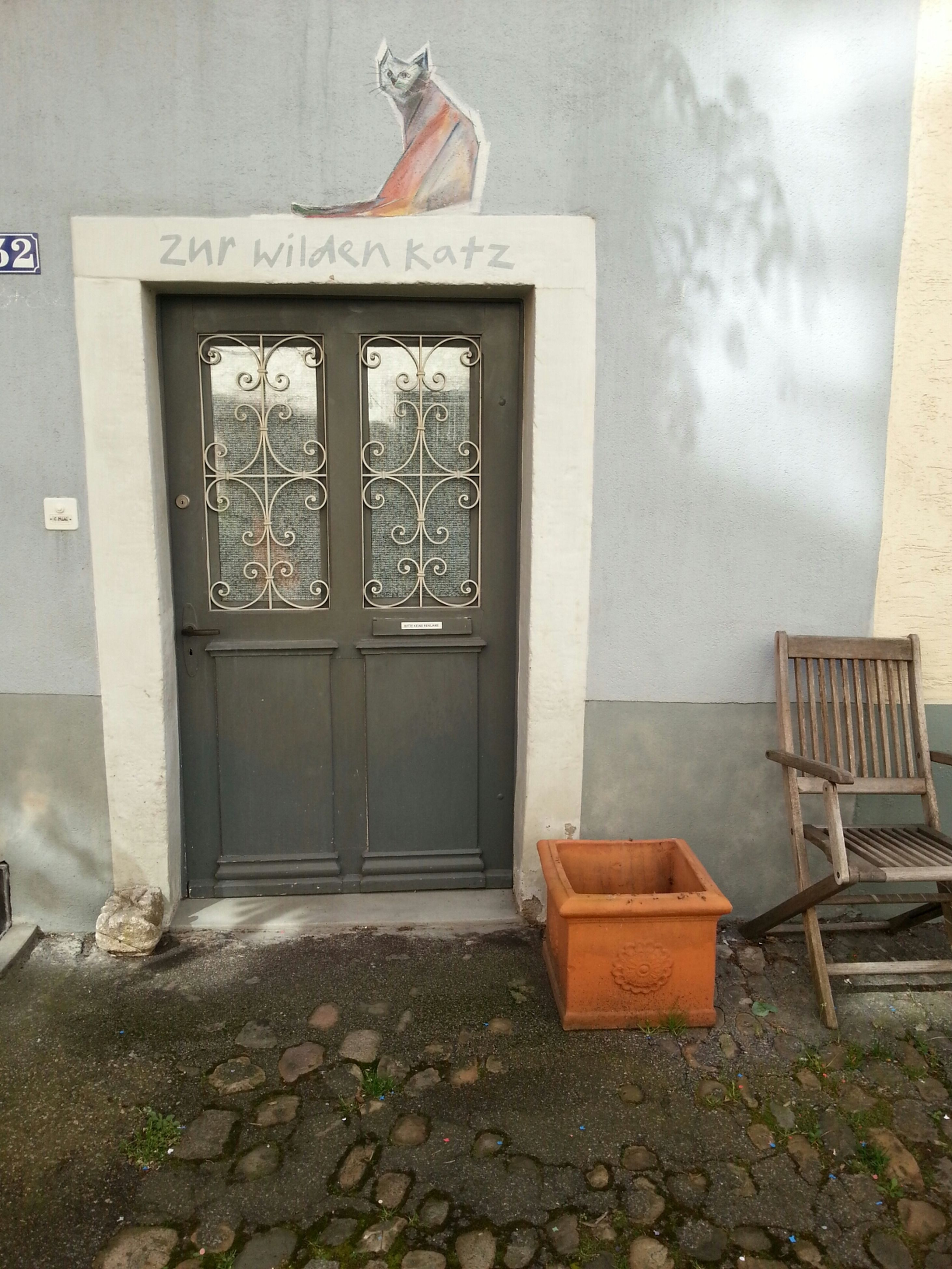 architecture, built structure, window, building exterior, door, house, closed, abandoned, wall - building feature, entrance, day, empty, old, glass - material, no people, cobblestone, text, obsolete, chair, absence