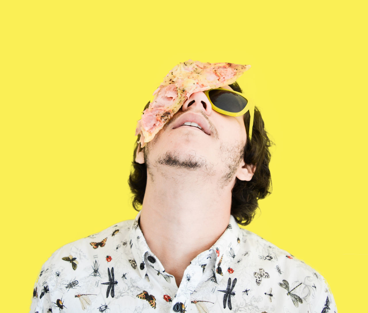 Young Man With Pizza On Face While Standing Against Yellow Background