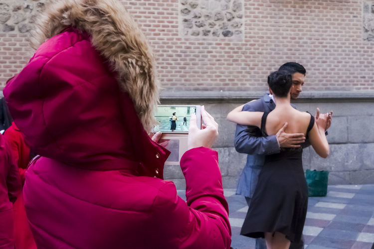 A tourist taking a photo of a young couple dancing the tango in Madrid. City City Life Dancing Man Mobile Phone Red Taking Photos Travel Travelling Woman Black Dancing Girl Editorial  Fall Leisure Activity Lifestyles Outdoors People Real People Rear View Standing Street Togetherness Two People Young Adult