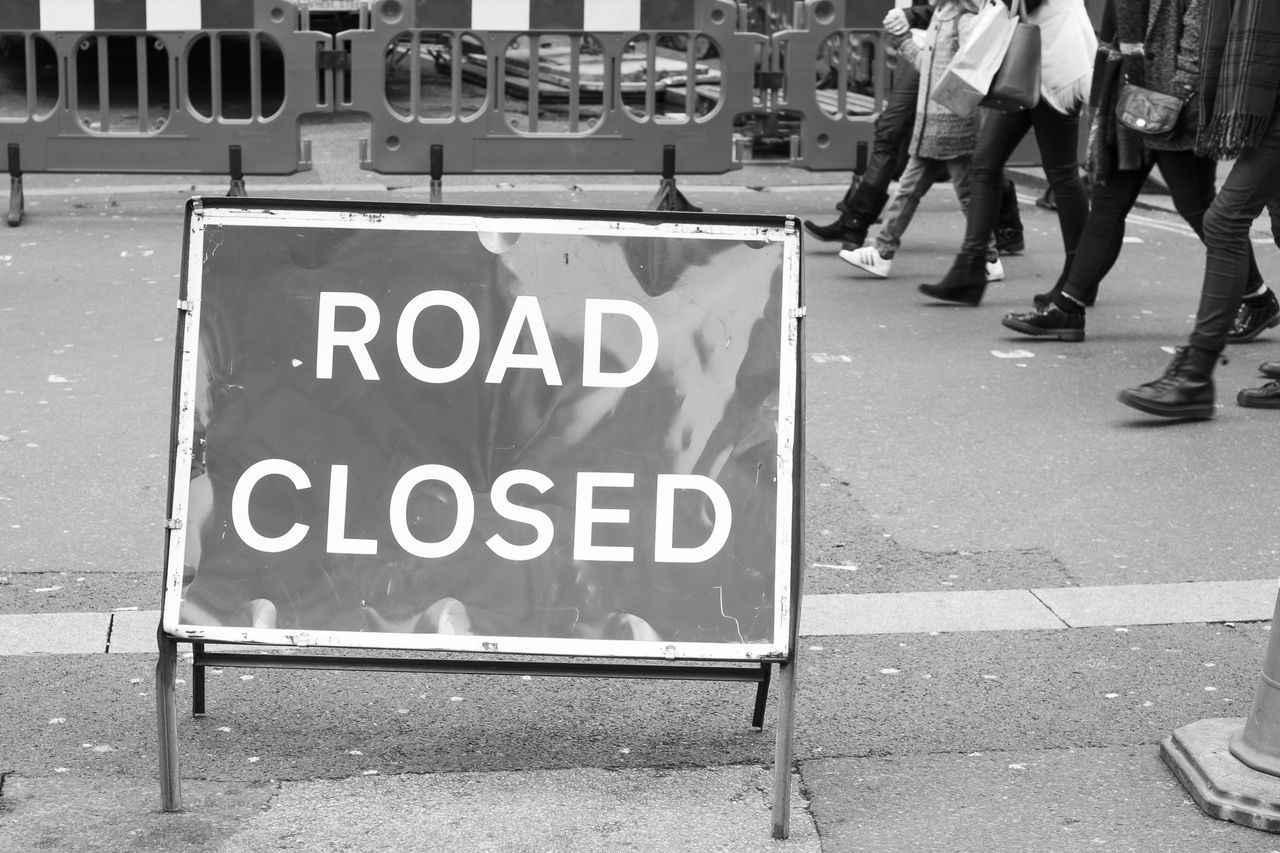 Road Closed Sign On Street With People Walking In Background