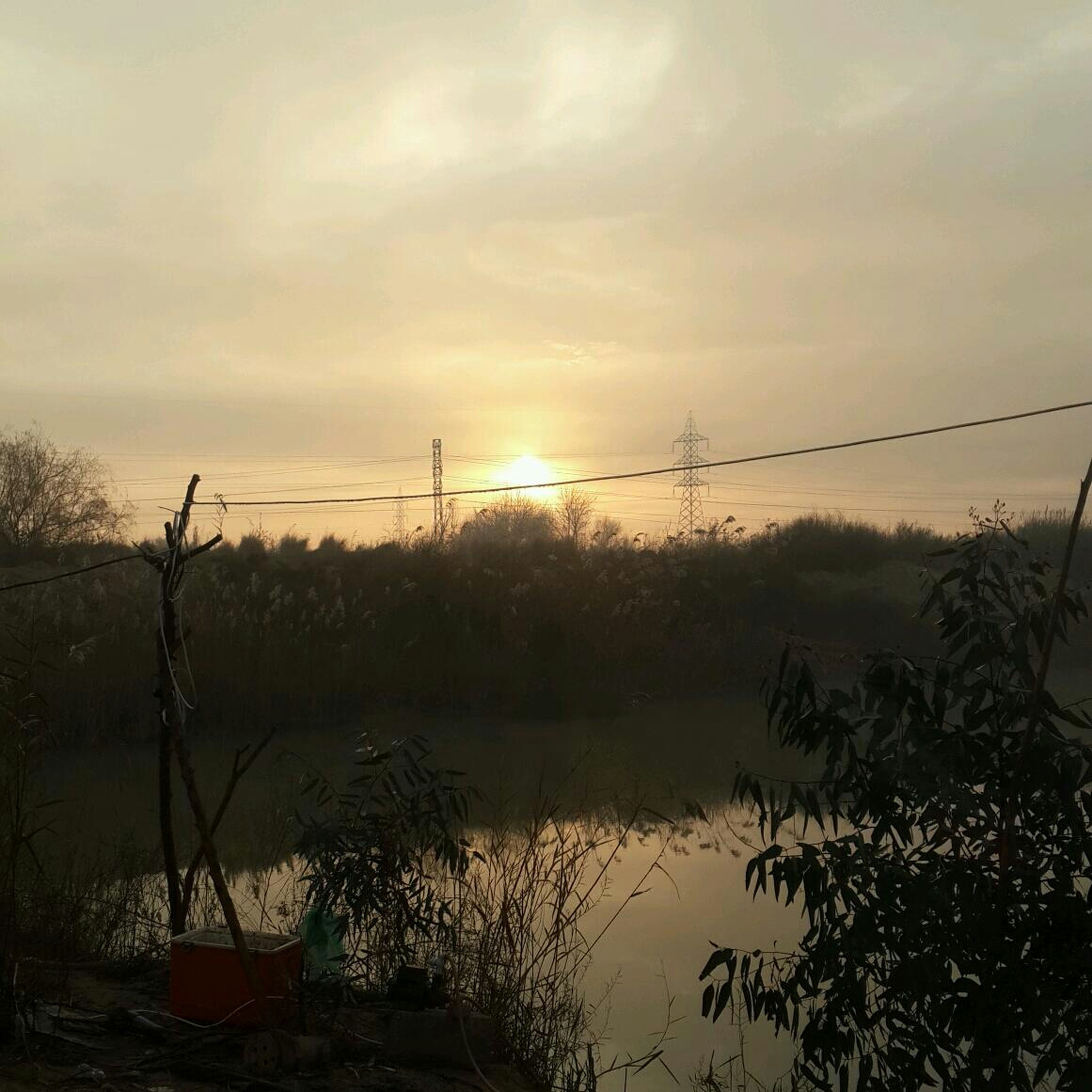 water, sunset, tranquility, sky, tranquil scene, scenics, lake, beauty in nature, reflection, tree, nature, silhouette, cloud - sky, idyllic, river, plant, orange color, cloud, sun, electricity pylon