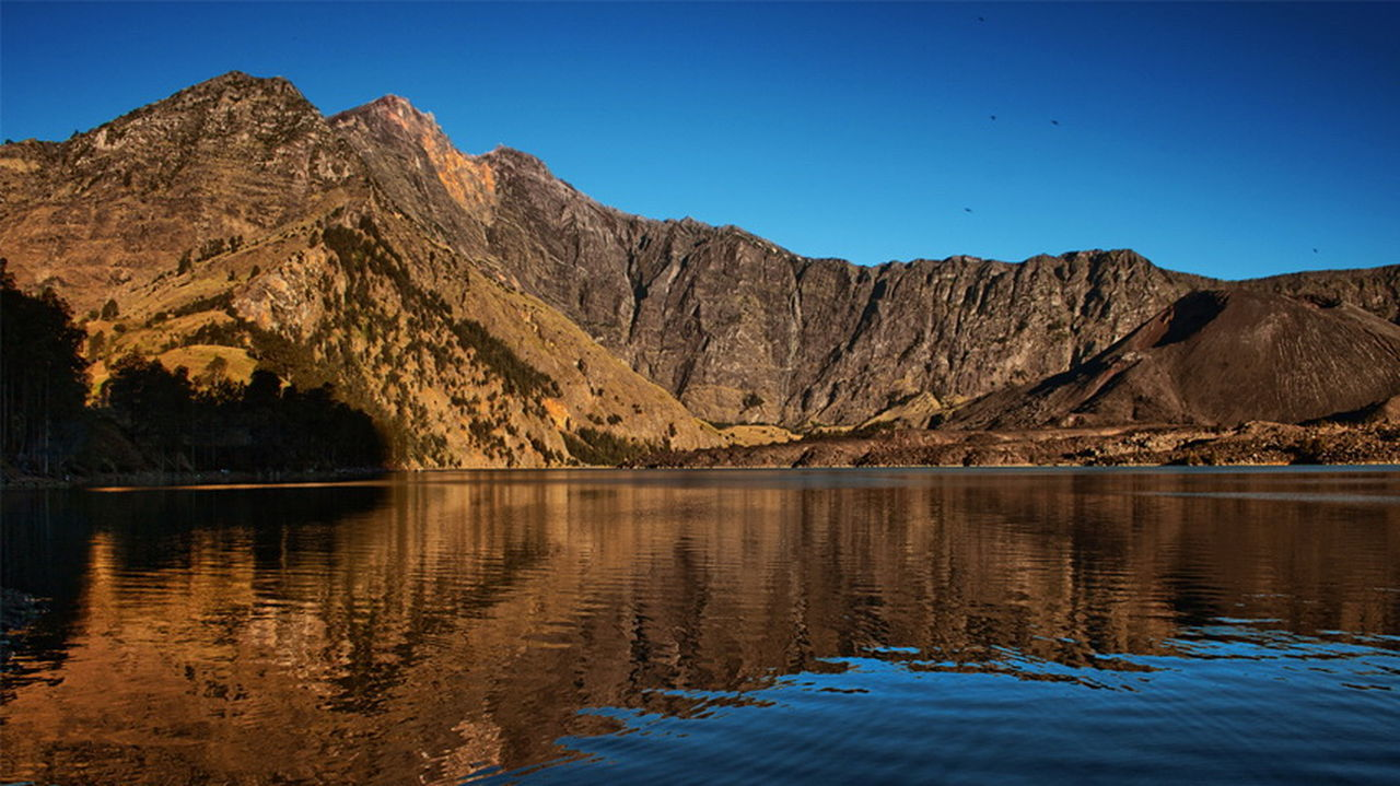 mountain, reflection, scenics, mountain range, tranquil scene, nature, tranquility, lake, beauty in nature, blue, waterfront, water, no people, clear sky, outdoors, day, landscape, sky, tree