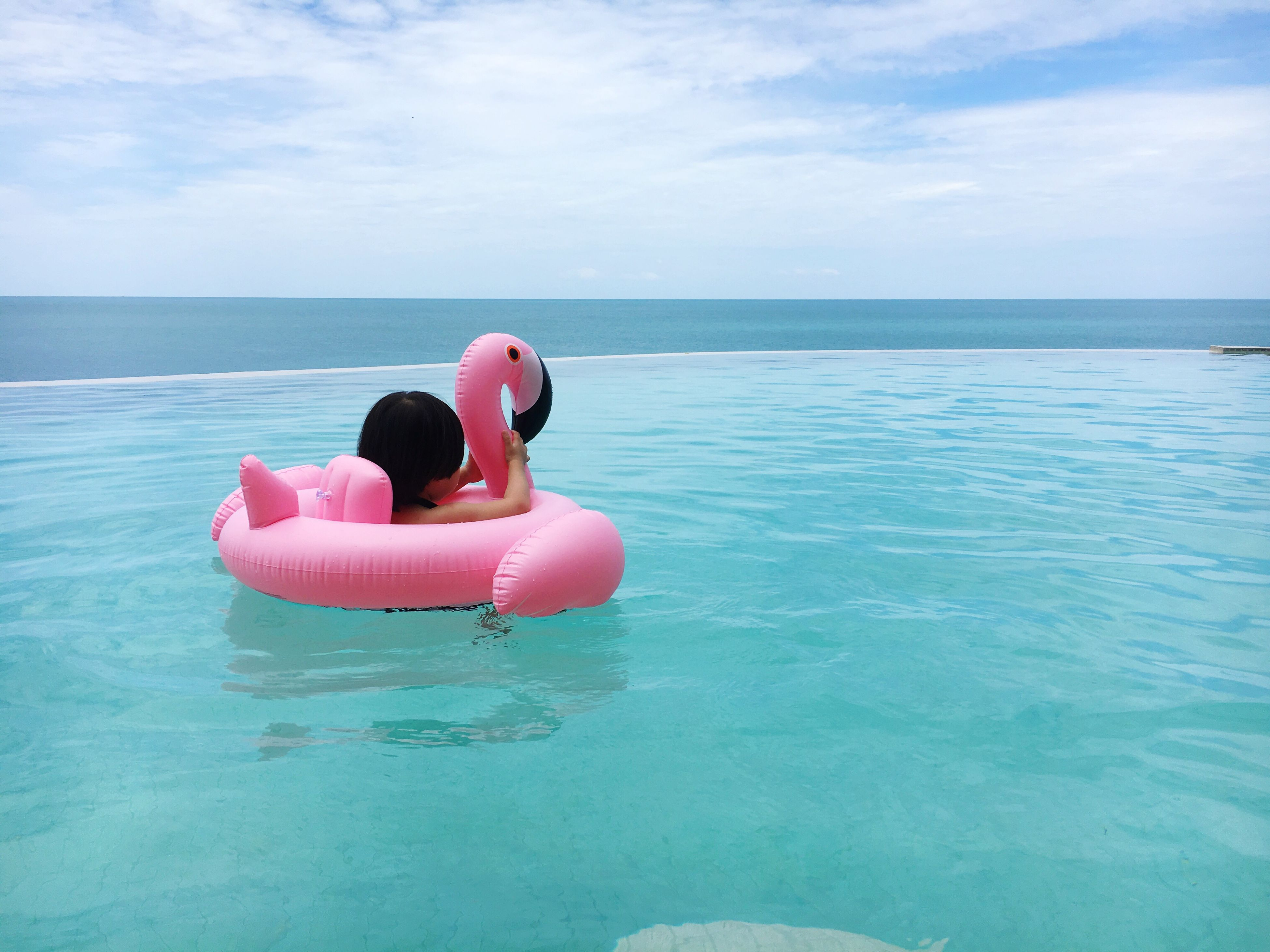 water, inflatable, sea, sky, horizon over water, inflatable ring, nature, pool raft, leisure activity, beauty in nature, one person, day, waterfront, real people, outdoors, floating on water, scenics, childhood, vacations, swimming pool, young women, young adult