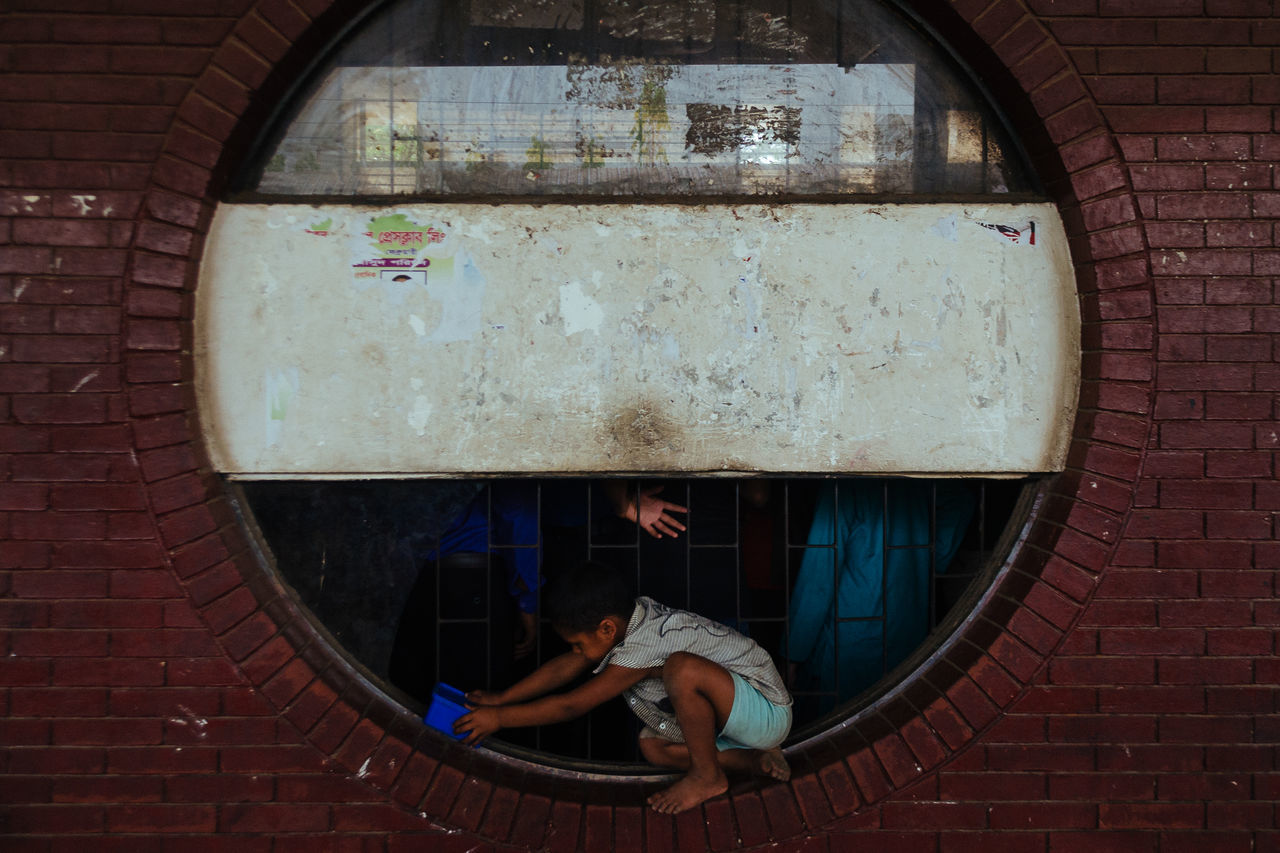 real people, window, brick wall, full length, one person, architecture, day, casual clothing, built structure, building exterior, lifestyles, outdoors, childhood, people