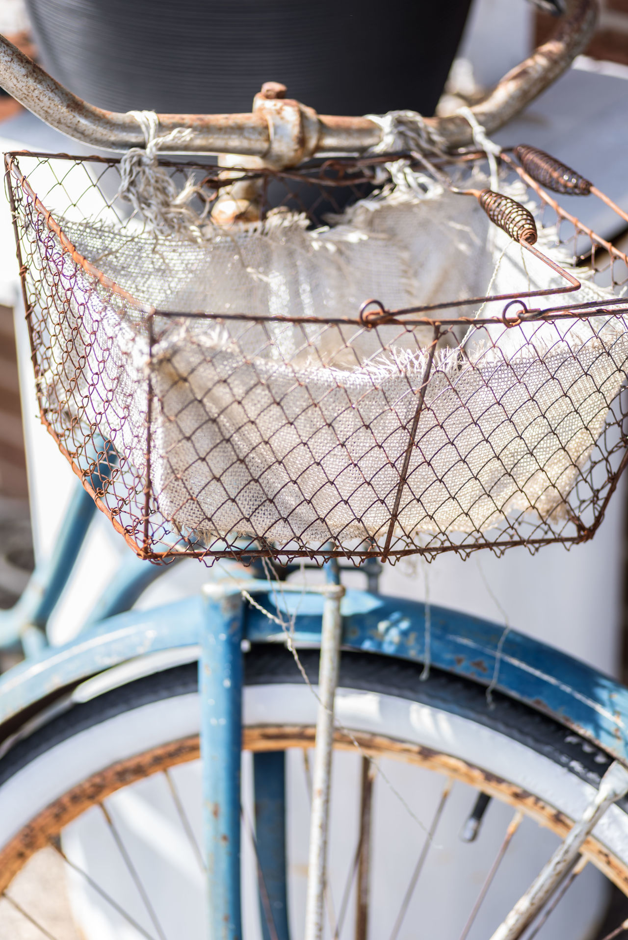 Old blue painted vintage bicycle with wire basket on rusty handlebars Selective Focus No People Spring Outdoors Day Macro Photography Soft Focus Vintage Bicycles Antique Bikes Retro Style Wire Basket Painted Rusty Metal Sunny Day Blue Color Cloth Bike Old Bike Rustic Style Garden Bike
