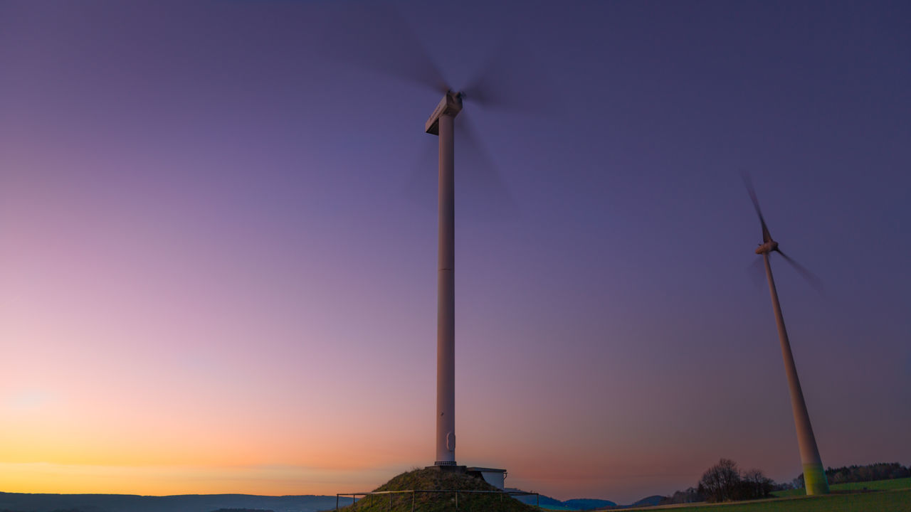 Low Angle View Of Windmills Against Romantic Sky