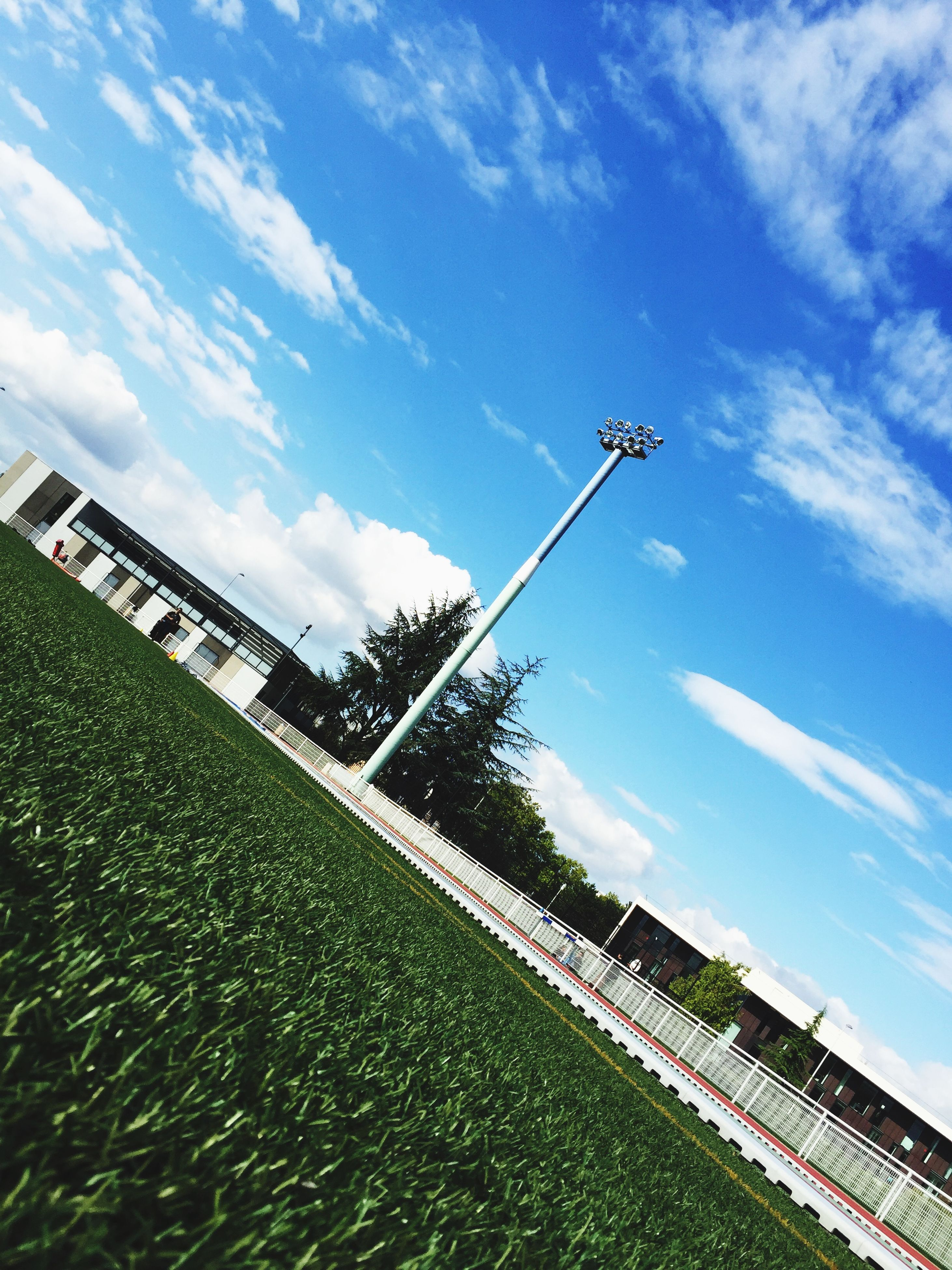 sky, low angle view, blue, cloud - sky, cloud, day, field, nature, tree, tranquility, grass, growth, connection, no people, tranquil scene, outdoors, cloudy, street light, sunlight, built structure