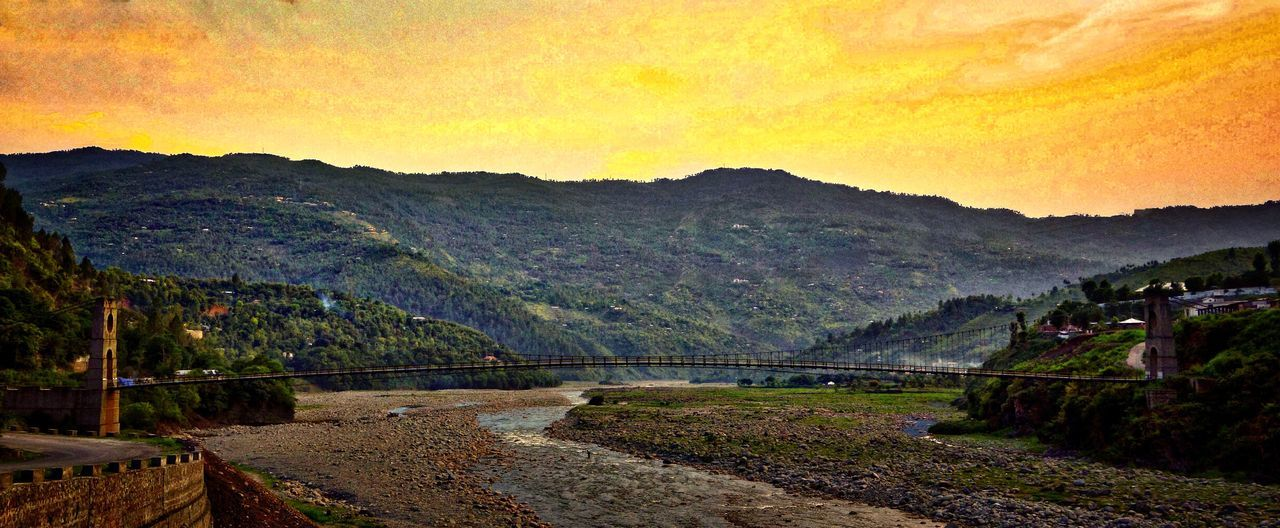 mountain, bridge - man made structure, connection, river, scenics, outdoors, nature, tranquil scene, beauty in nature, water, tranquility, no people, landscape, mountain range, architecture, sky, built structure, tree, day