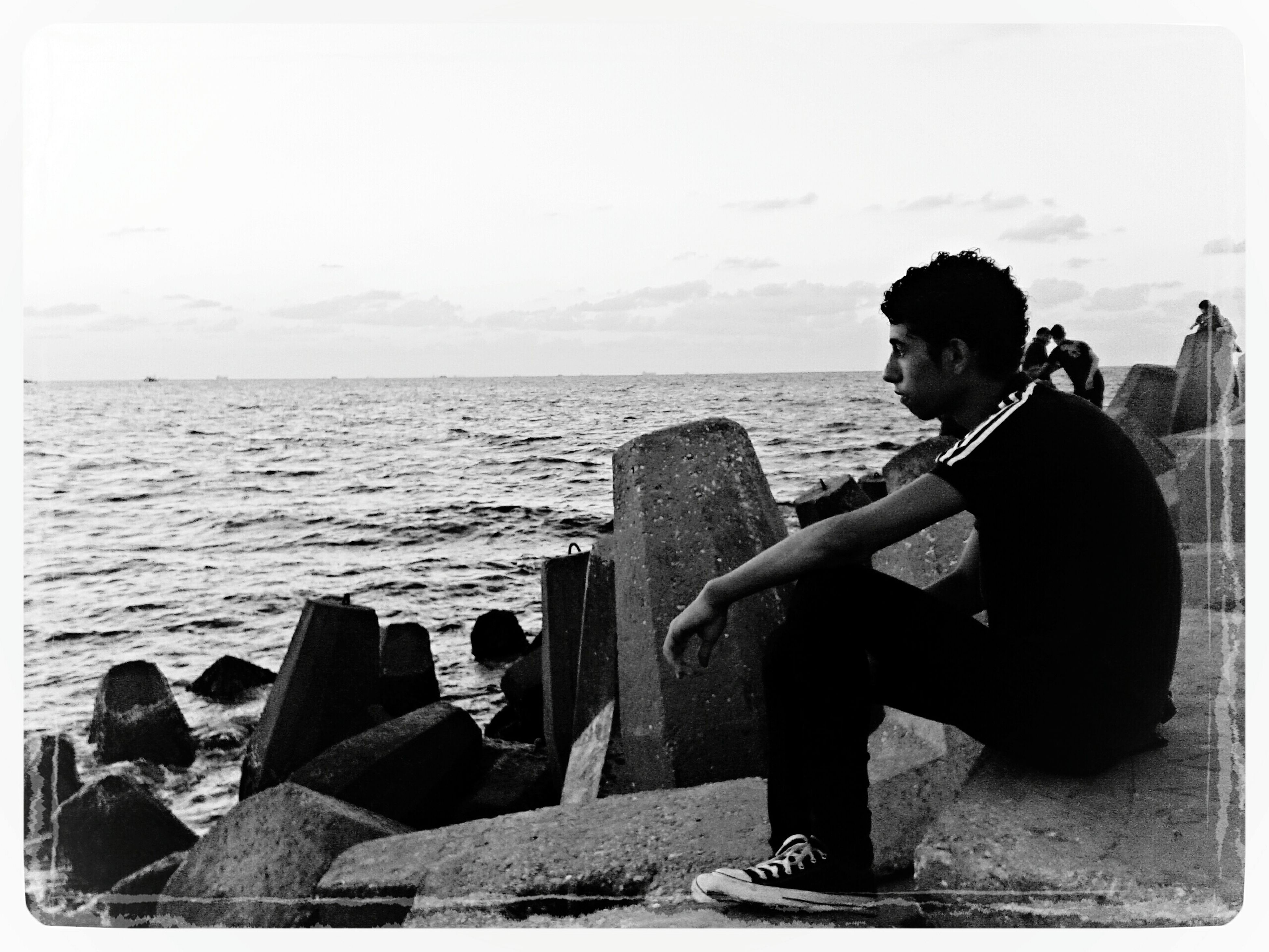 sea, water, horizon over water, lifestyles, sitting, leisure activity, young adult, rear view, full length, sky, casual clothing, standing, photography themes, person, looking at view, relaxation, photographing, young women