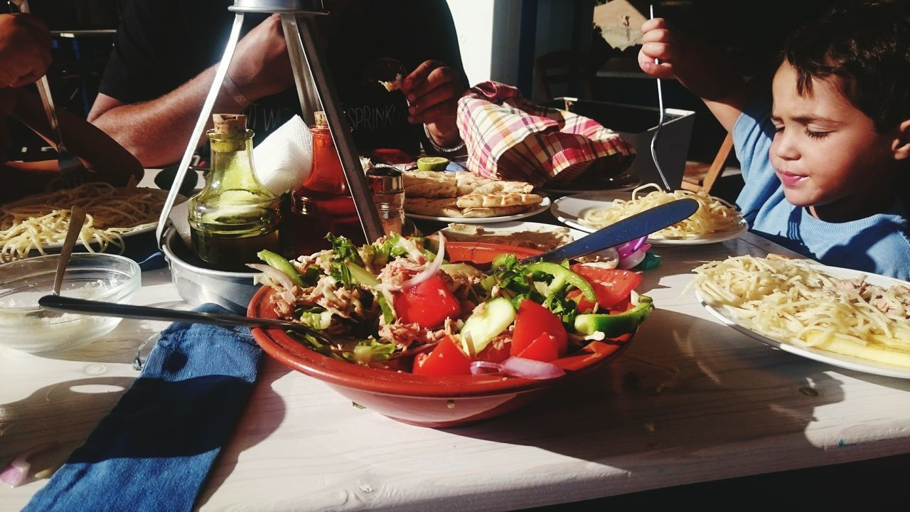 food and drink, food, indoors, real people, salad, table, bowl, plate, freshness, boys, eating, healthy eating, lifestyles, ready-to-eat, sitting, two people, lettuce, human hand, close-up, mexican food, day, people