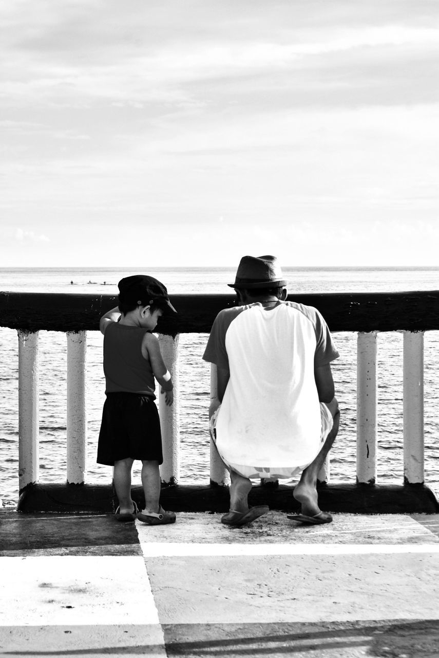 sea, rear view, two people, full length, beach, togetherness, real people, water, men, sitting, women, leisure activity, horizon over water, sky, friendship, outdoors, day, lifestyles, nature, relaxation, bonding, adult, people
