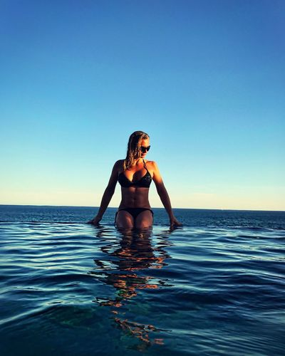 Infinity Pool Swimming Pool Ocean Water Water Reflections Water_collection Evening Sunset Vacations Bikini Woman Relaxing Sea Blue Lifestyles Clear Sky Horizon Over Water Leisure Activity One Person Beautiful Woman Outdoors Travel Resort Luxury Destination