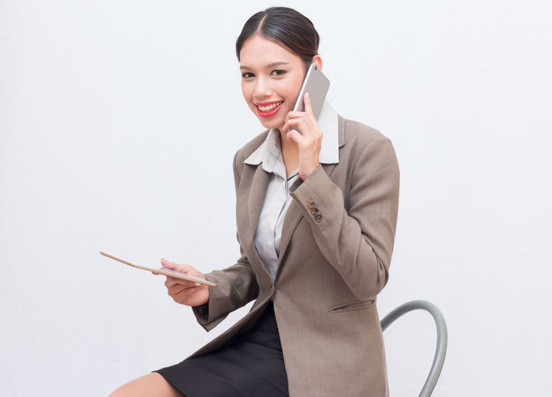 Businesswoman use of mobile phone. young woman used smart phone and tablet. Answering Business Businesswoman Communication Connection Happiness Holding Listening Looking At Camera Mobile Phone Occupation One Person Portable Information Device Smiling Studio Shot Suit Talking Technology Using Phone Well-dressed White Background Wireless Technology Women Young Adult Young Women