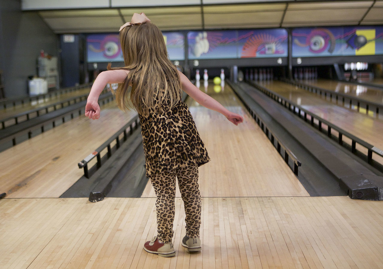 A five-year-old girl waits for the bowling ball to strike a pin. Almost Got It Blond Hair Bowling Bowling Alley Canon Canon 1DC Childhood Competition COMPTITION Family Five-year-old Full Length Fun Indoors  One Person Sports