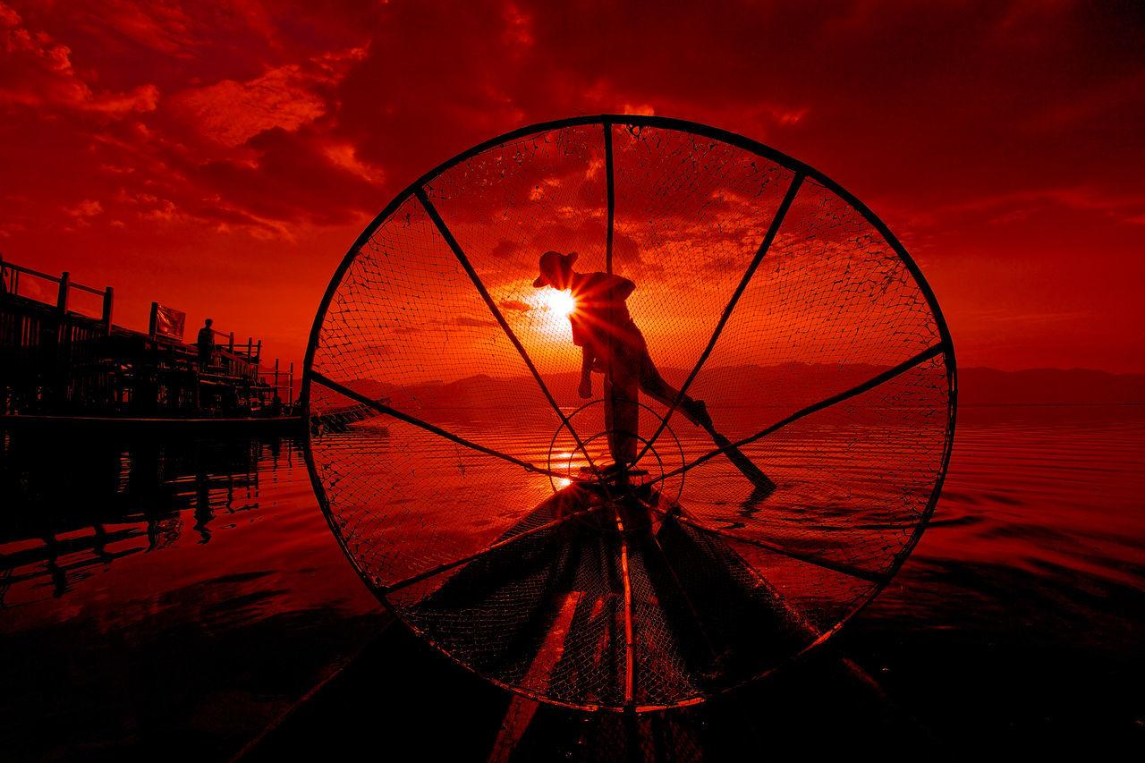 Fisherman Standing On Boat Seen Through Fishing Net During Sunset