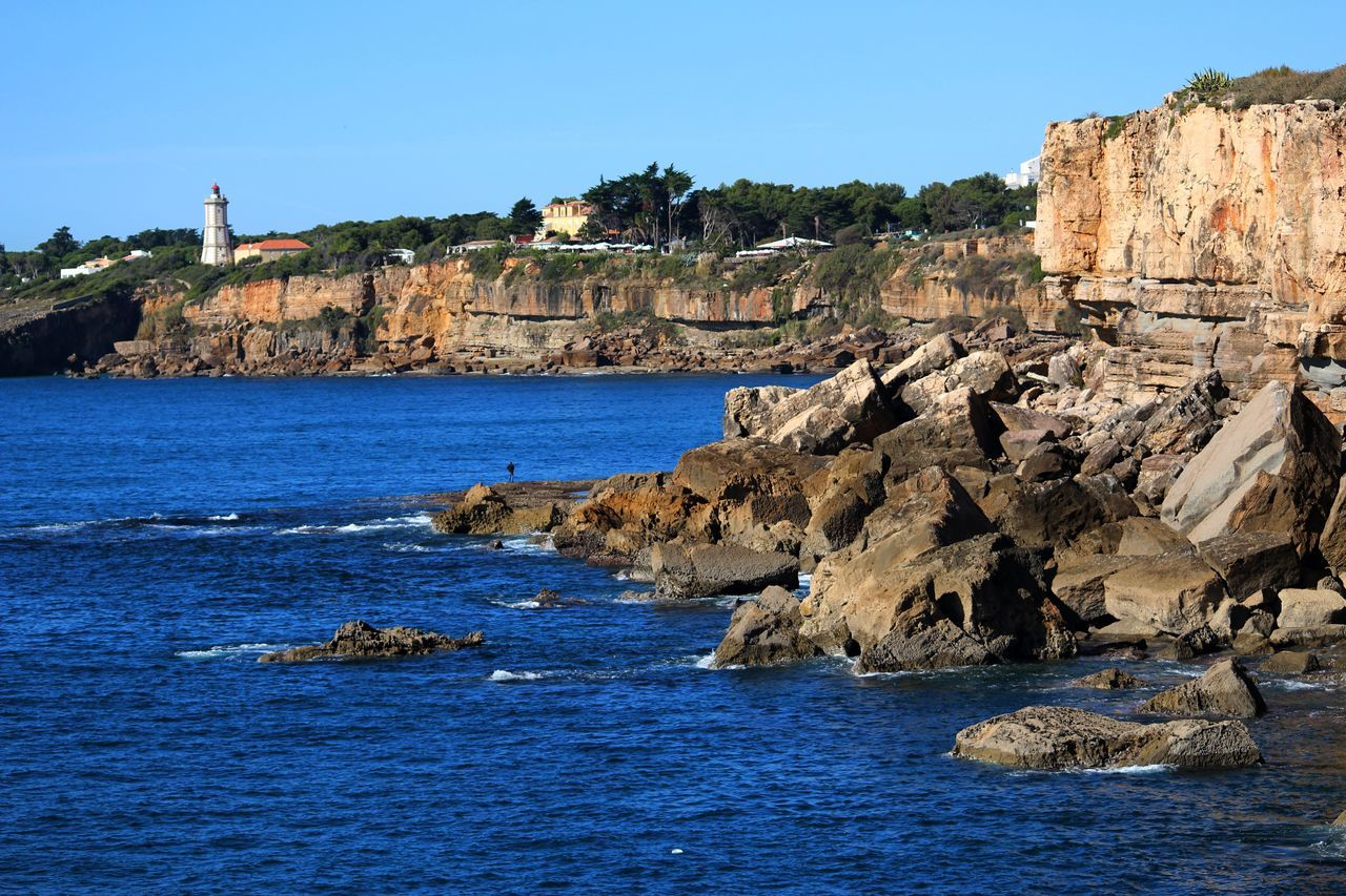 Architecture Blue Building Building Exterior Built Structure Clear Sky Cliff Coastline Exceptional Photographs EyeEm Best Shots Finding New Frontiers Lighthouse Nature Ocean Outdoors Places Plants Portugal Rock Rock - Object Rocks Shore Sky Trees Water