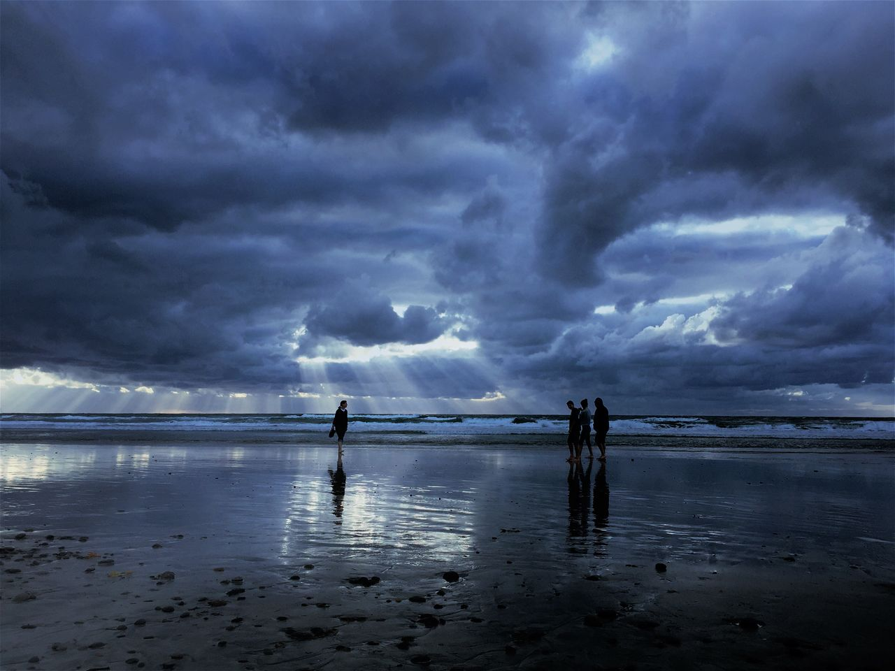 People At Beach Against Storm Clouds