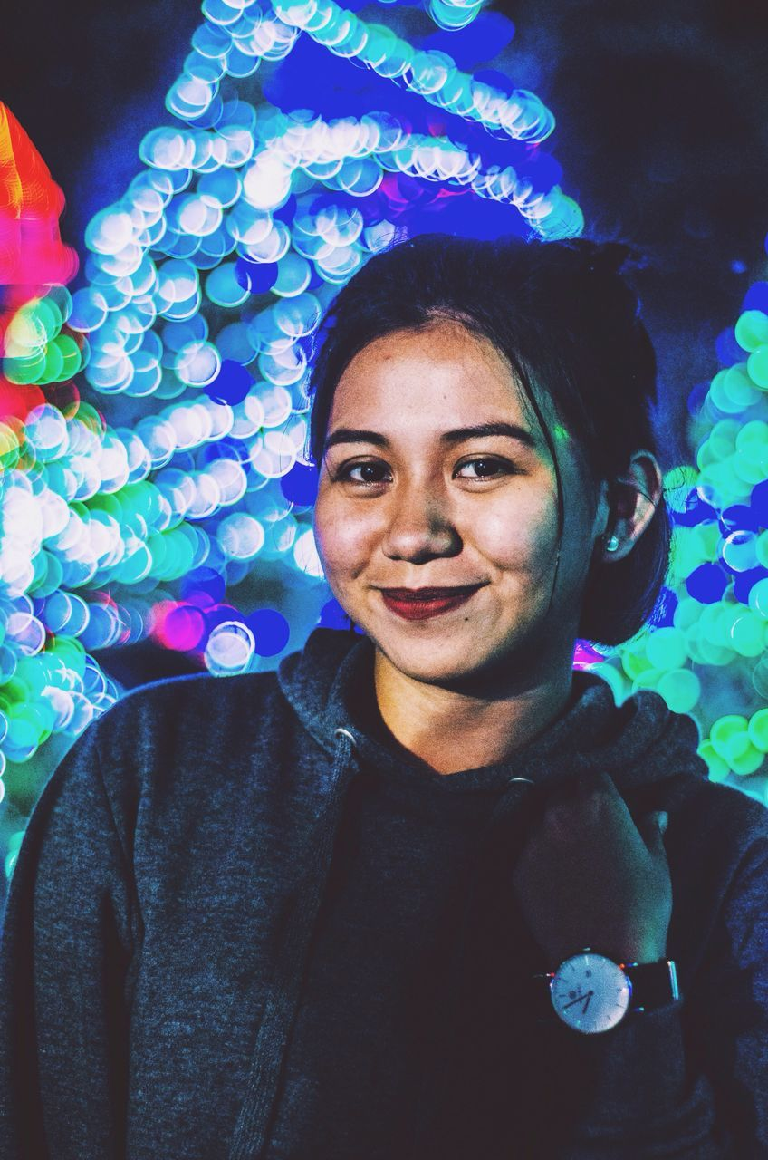 real people, looking at camera, portrait, front view, one person, smiling, lifestyles, leisure activity, happiness, young adult, multi colored, indoors, headshot, night, celebration, young women, cheerful, close-up