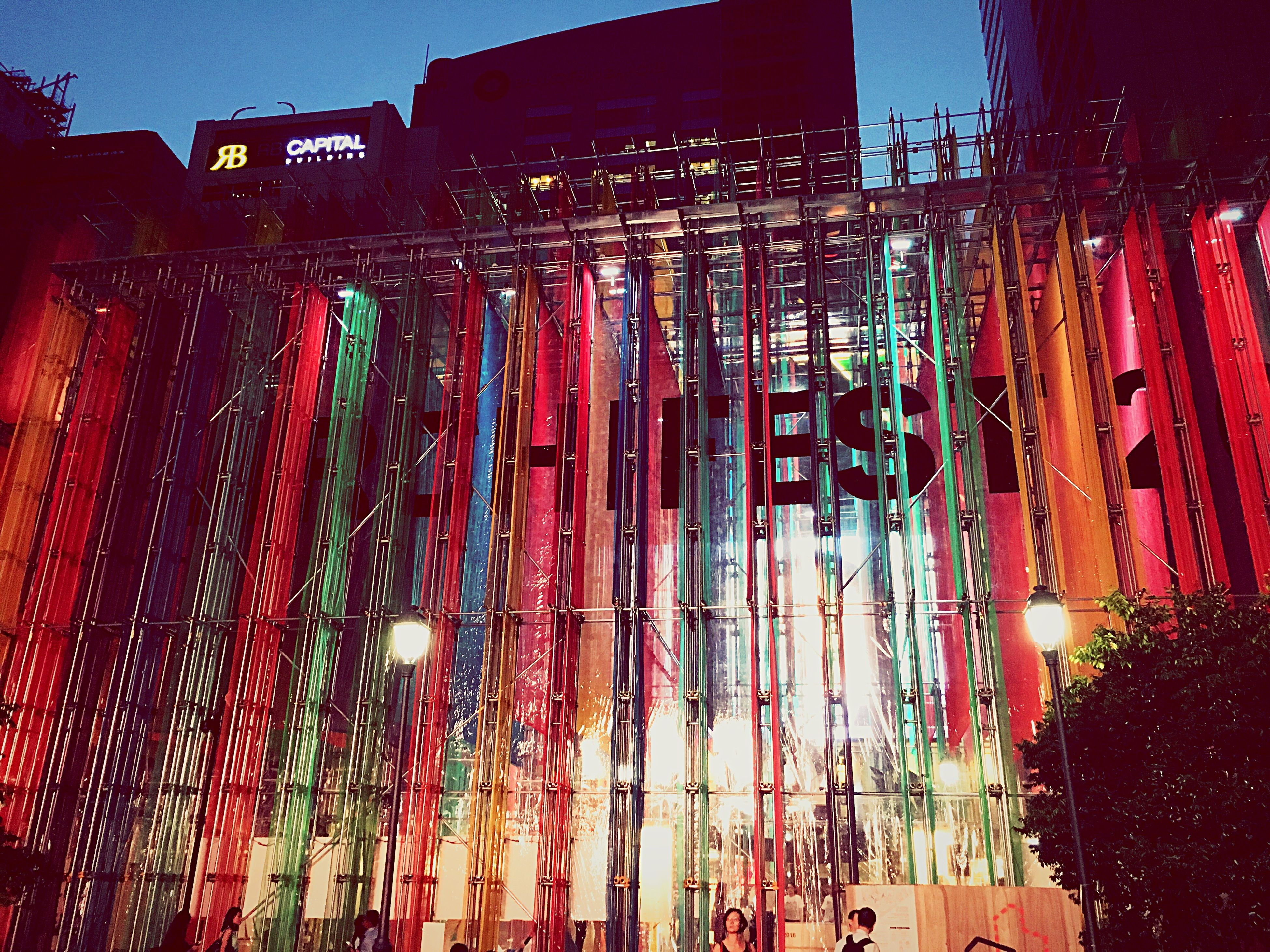 architecture, built structure, window, low angle view, building exterior, multi colored, illuminated, red, decoration, electric light, outdoors, office building, no people, pink color