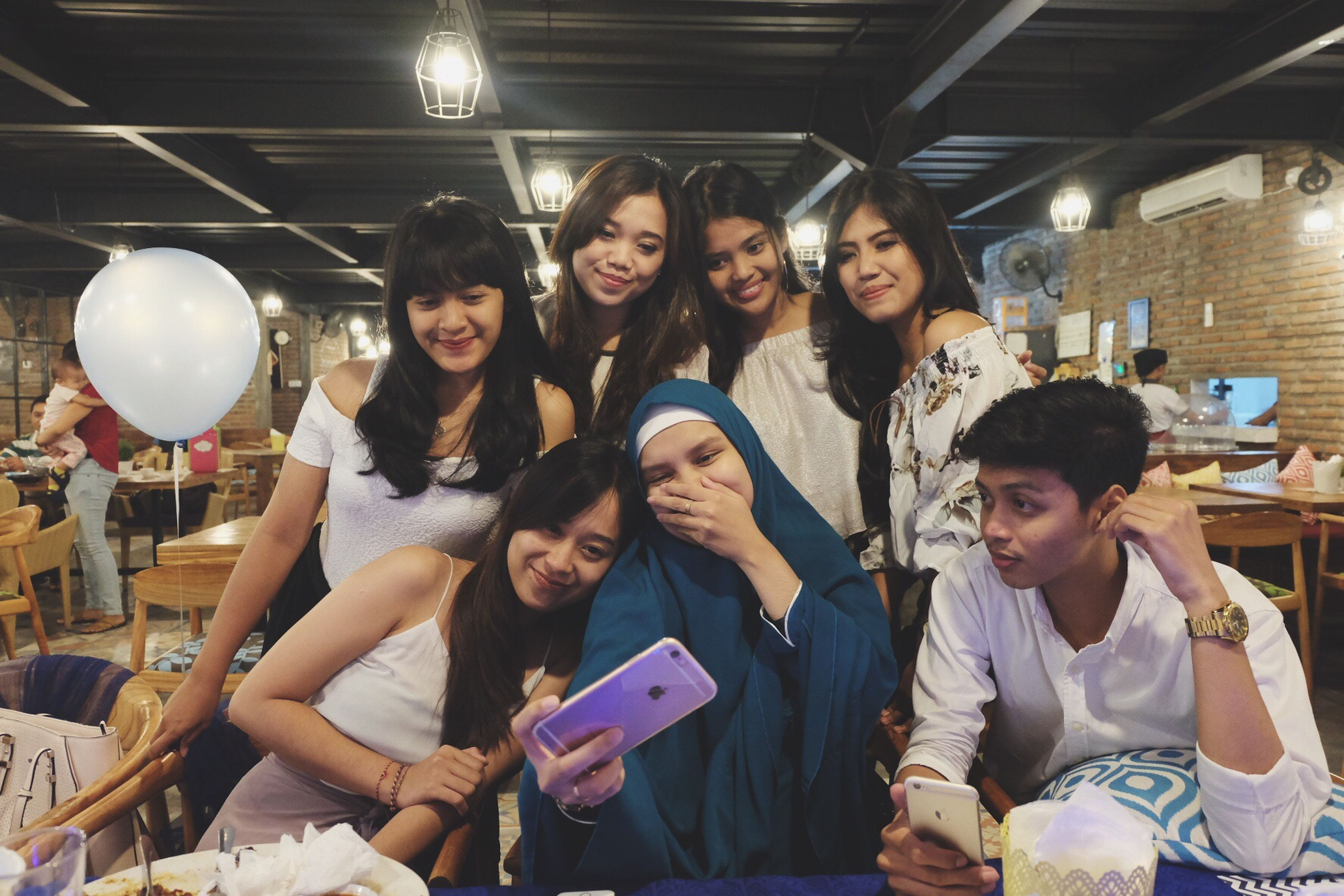 wireless technology, mobile phone, communication, portable information device, technology, smart phone, real people, looking at camera, smiling, indoors, holding, portrait, casual clothing, leisure activity, young women, happiness, togetherness, sitting, young adult, lifestyles, friendship, cheerful, selfie, photo messaging, day