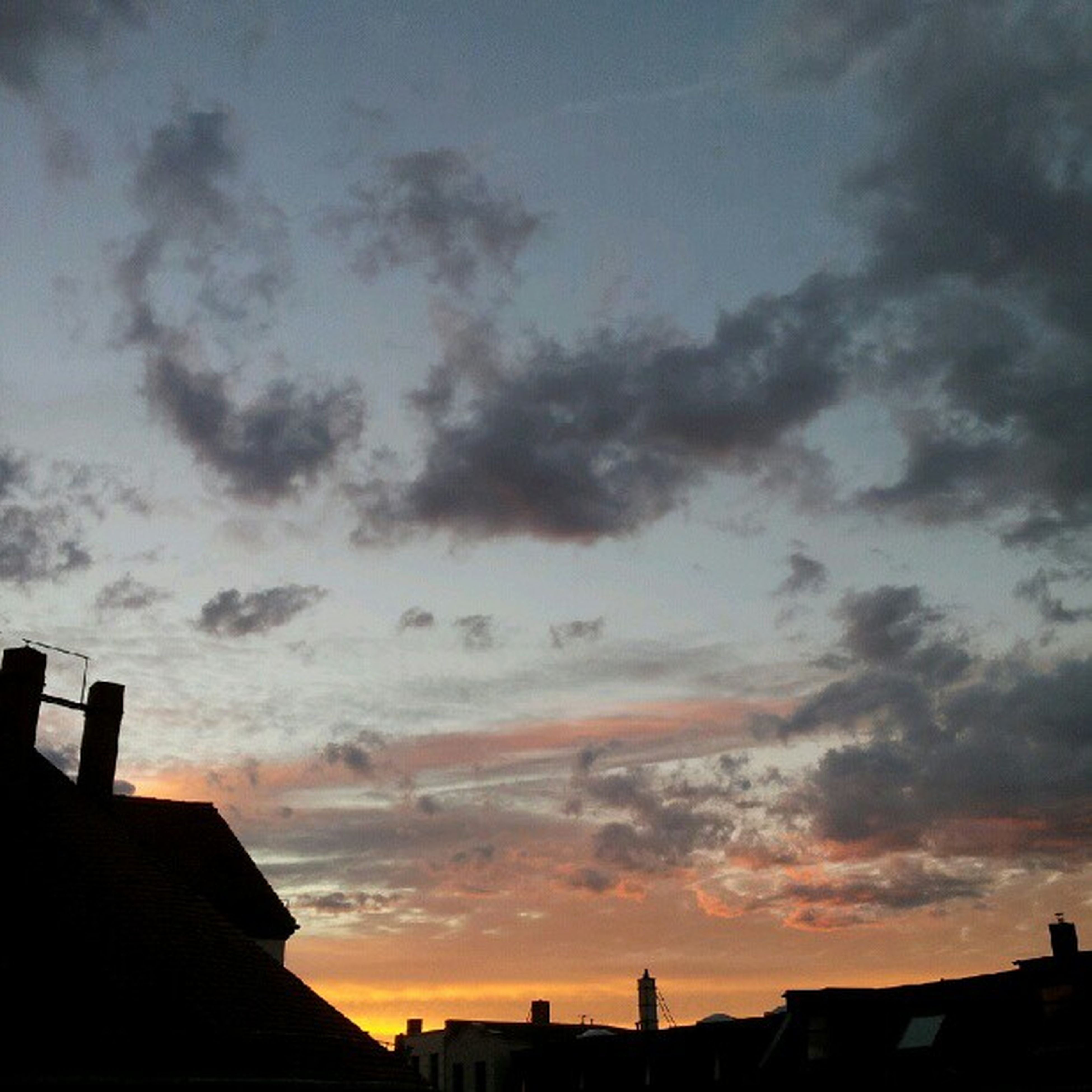 building exterior, architecture, built structure, sunset, silhouette, sky, cloud - sky, low angle view, city, cloudy, cloud, residential structure, house, building, residential building, dusk, high section, orange color, outdoors, dramatic sky