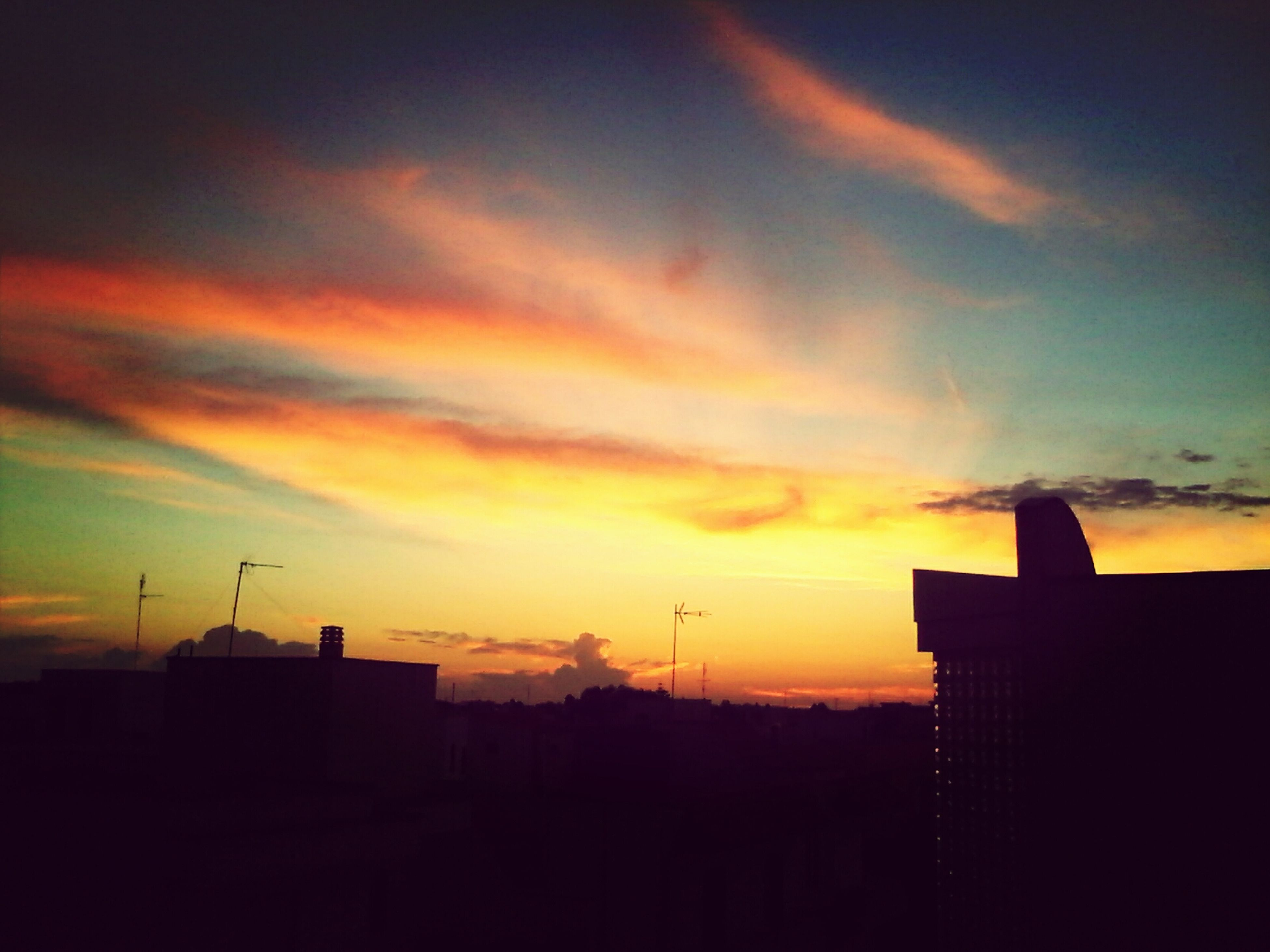 sunset, silhouette, building exterior, built structure, architecture, sky, orange color, cloud - sky, dramatic sky, beauty in nature, cloud, scenics, dark, outline, city, nature, cloudy, building, moody sky, low angle view